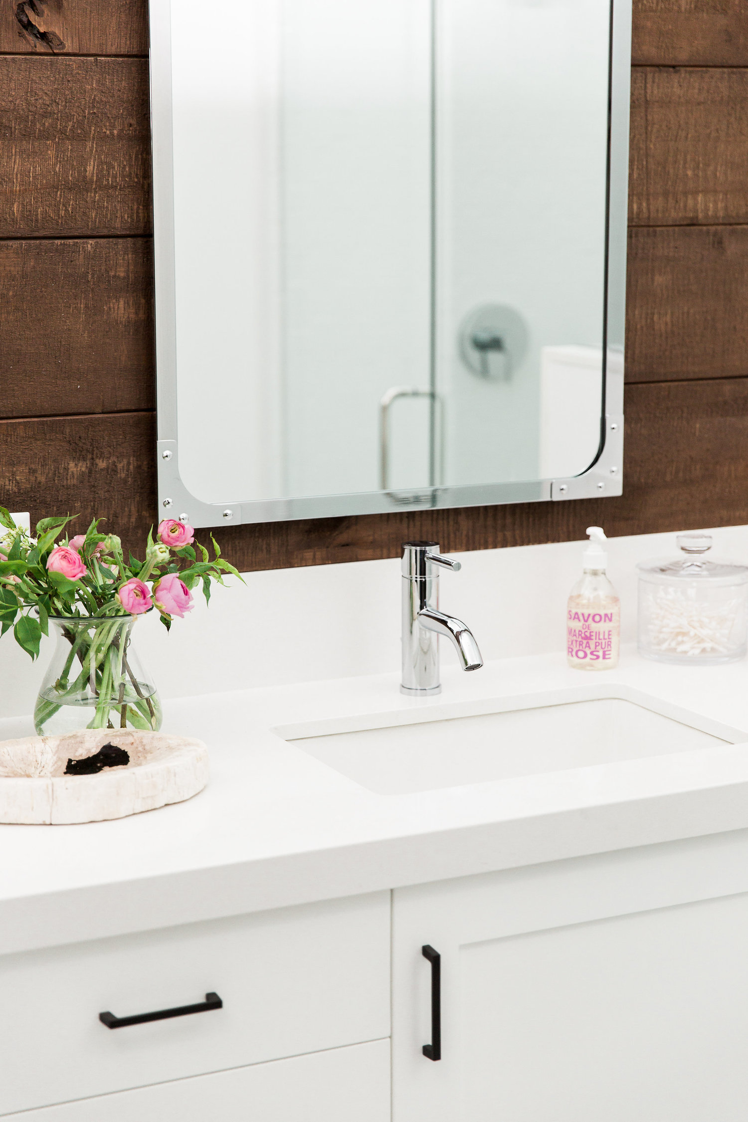 Mirror hanging above bathroom sink