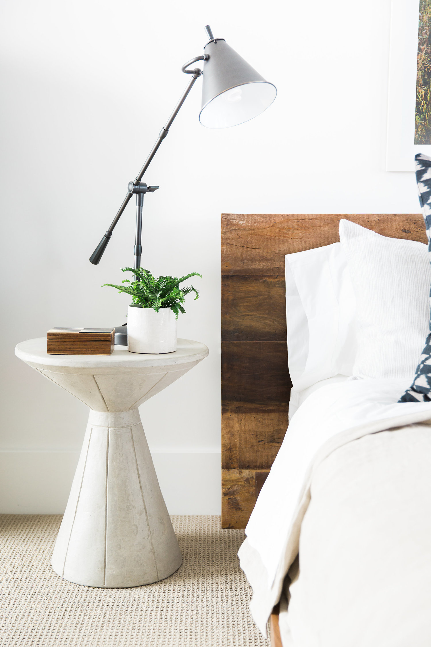 White circular nightstand next to bed