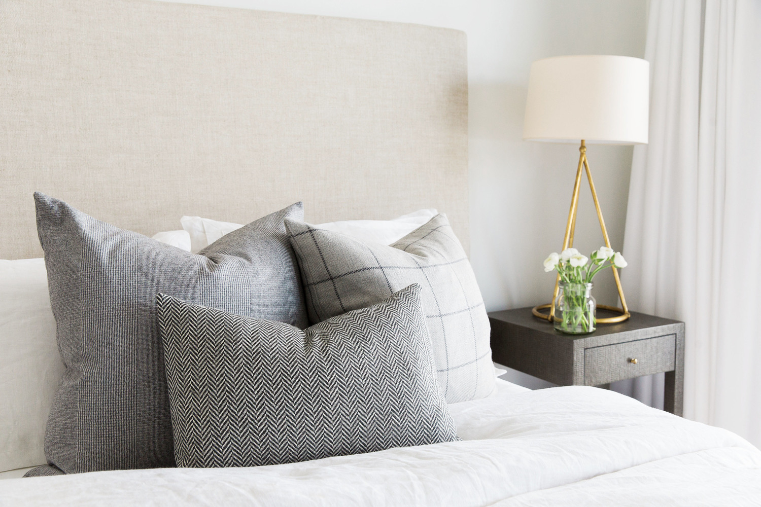 Decorative pillows on white bed in bedroom