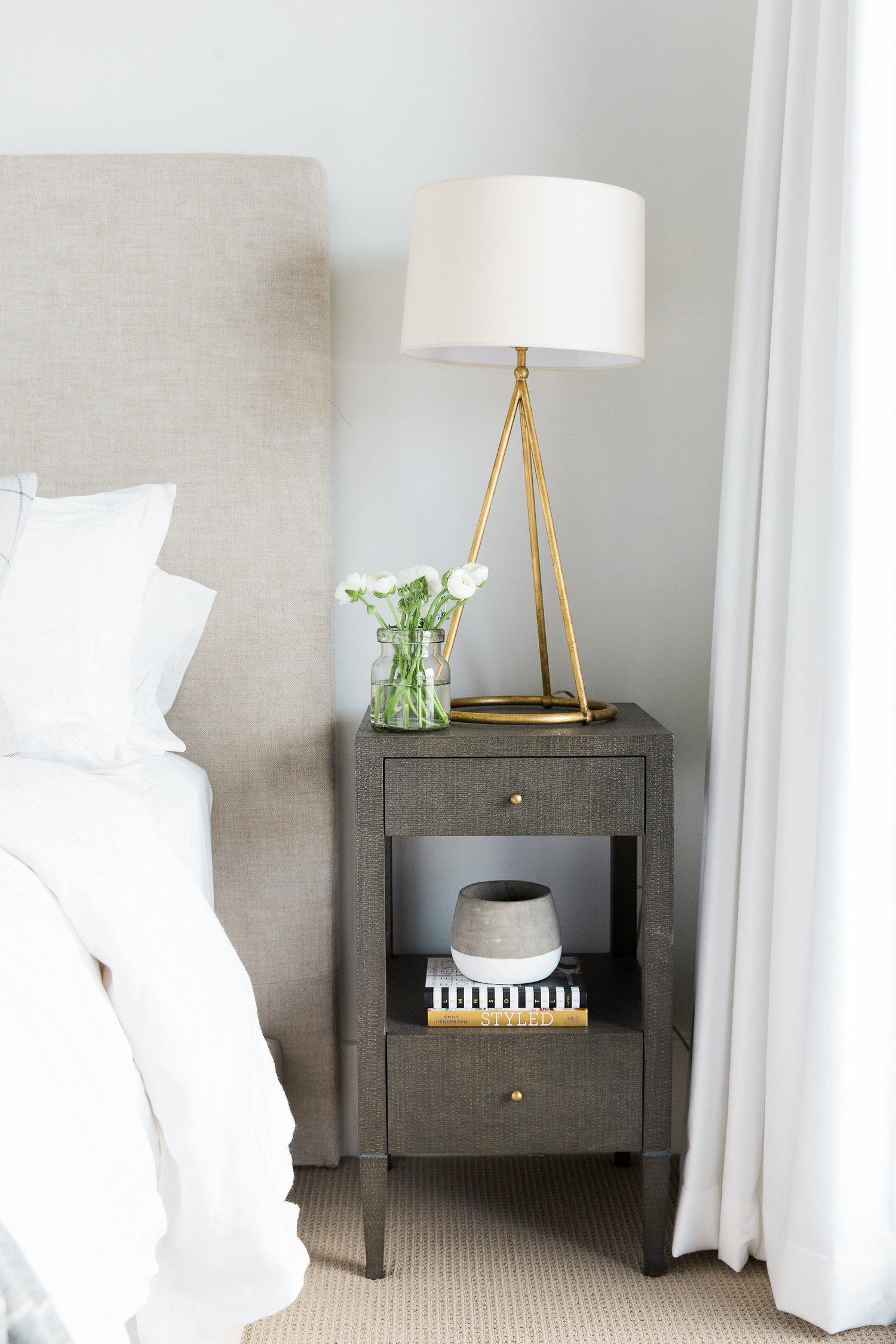 Small, dark nightstand next to bed