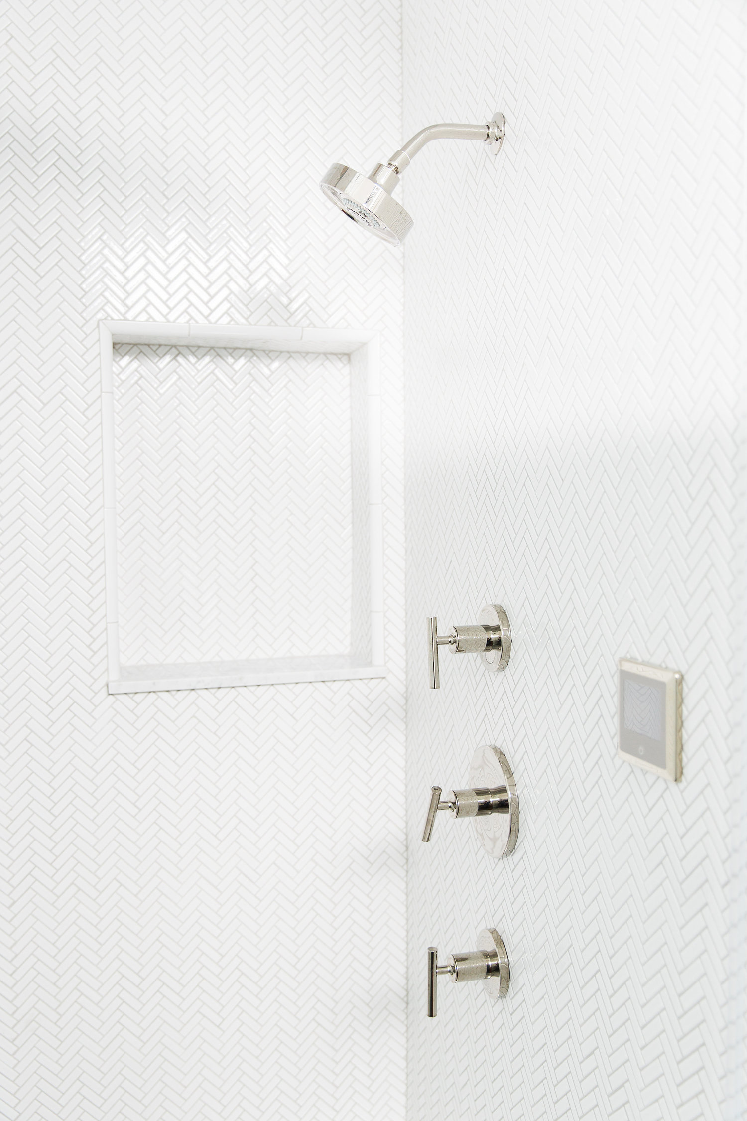 White bathroom shower with silver accents