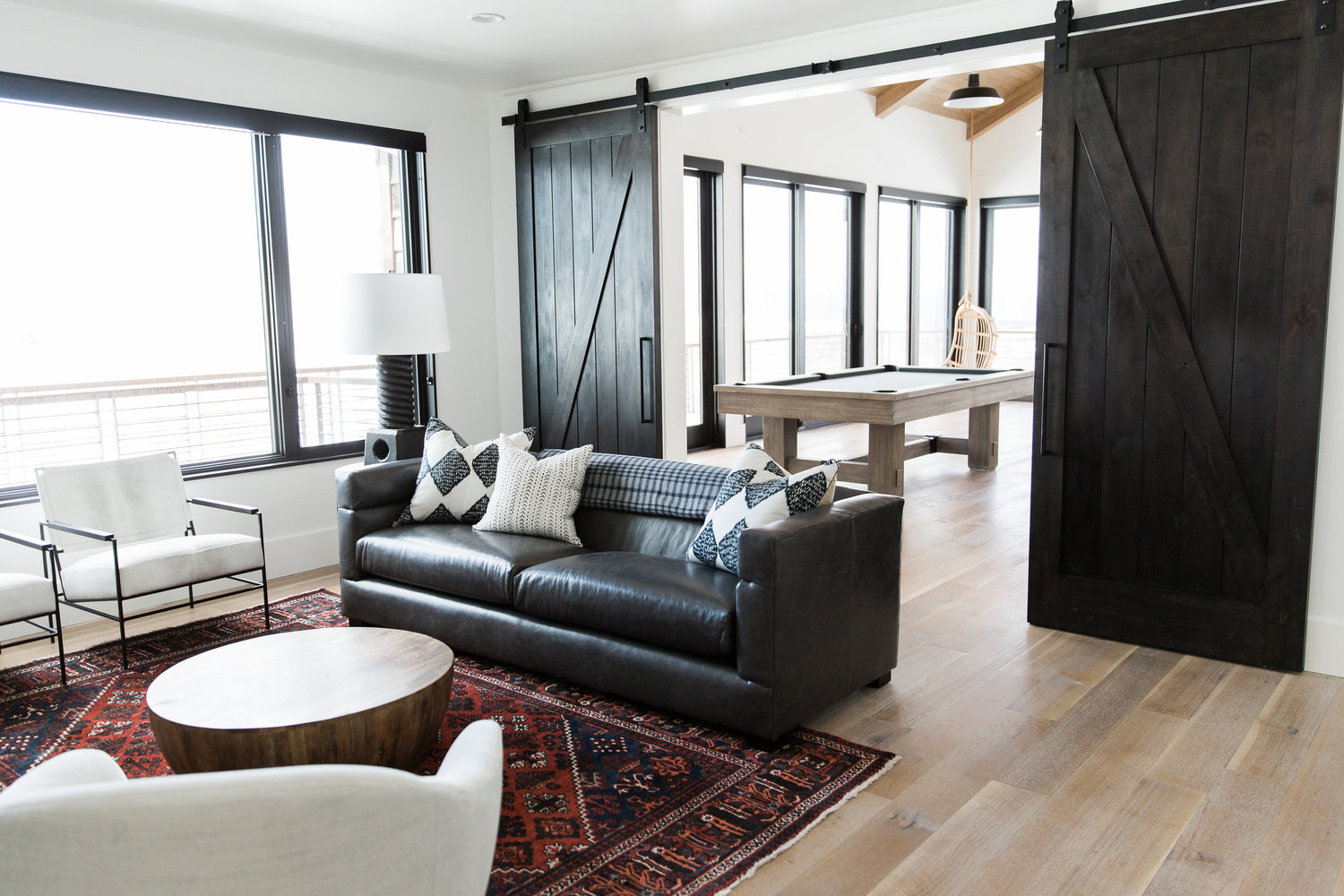 Large brown couch in front of double barn doors