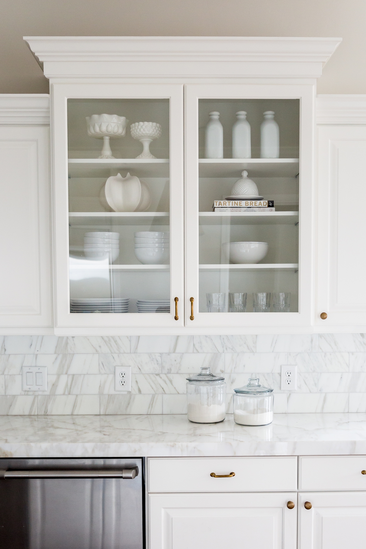 White glass cabinet full of dishes in kitchen