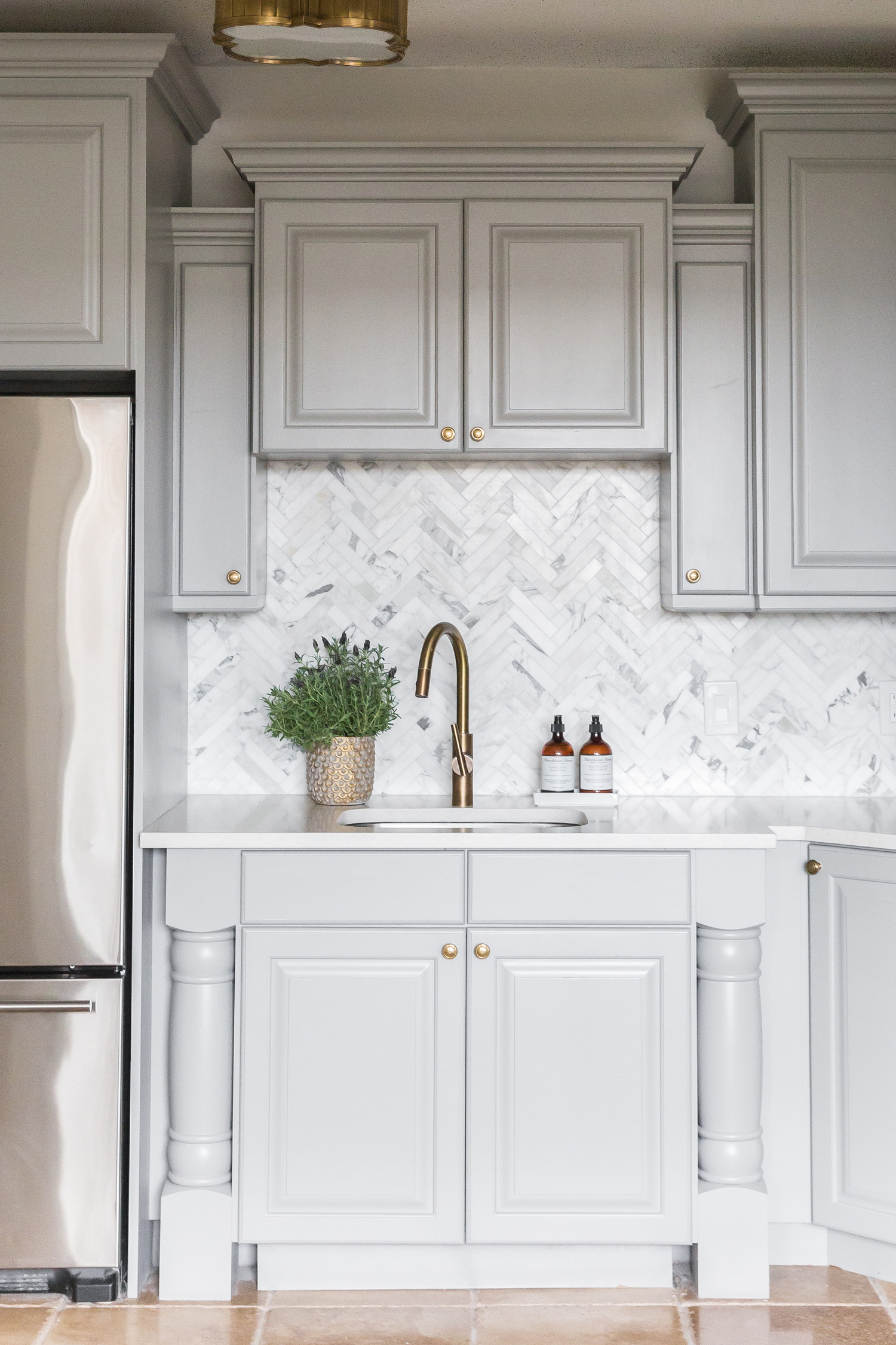 White kitchen cabinets with brass faucet