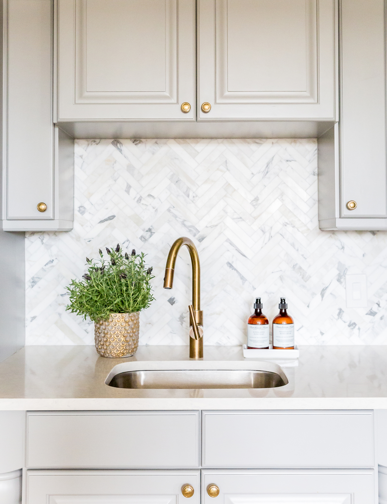 Brass faucet in front of white backsplash