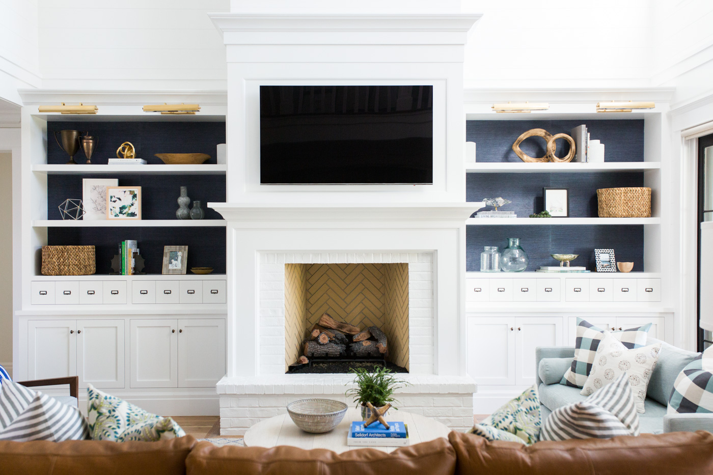 White brick fireplace with navy grasscloth in built-ins || Studio McGee