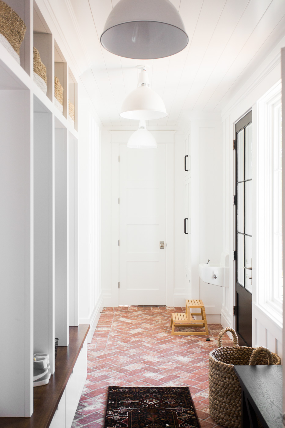 Brick herringbone and board-and-batten walls in the mudroom || Studio McGee