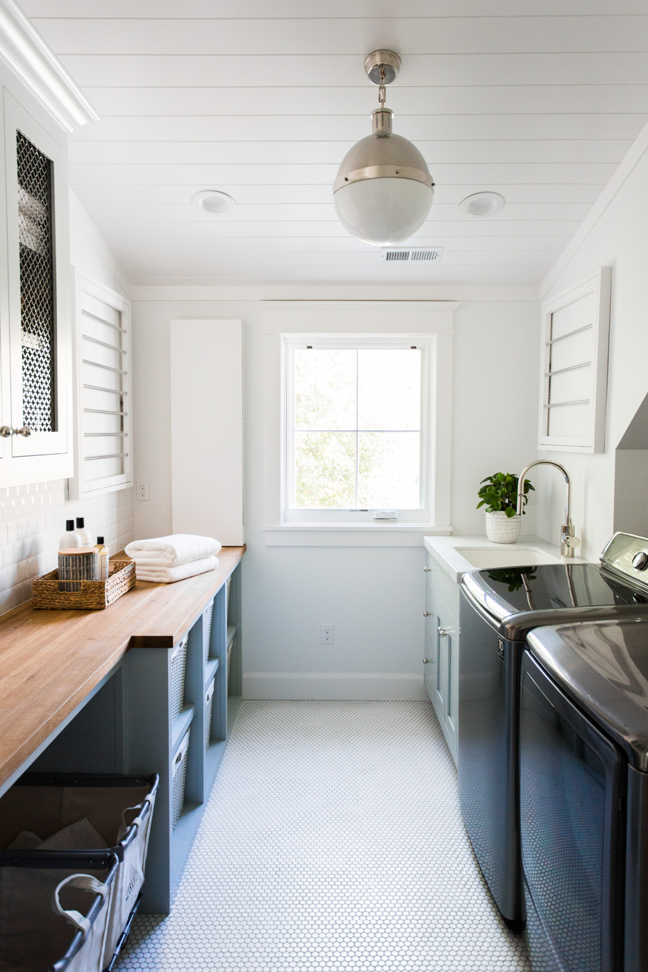 Green cabinets with butcher blog, white penny tile laundry room || Studio McGee