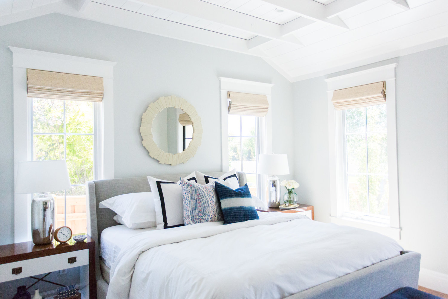 White bed with headboard and mirror on back wall