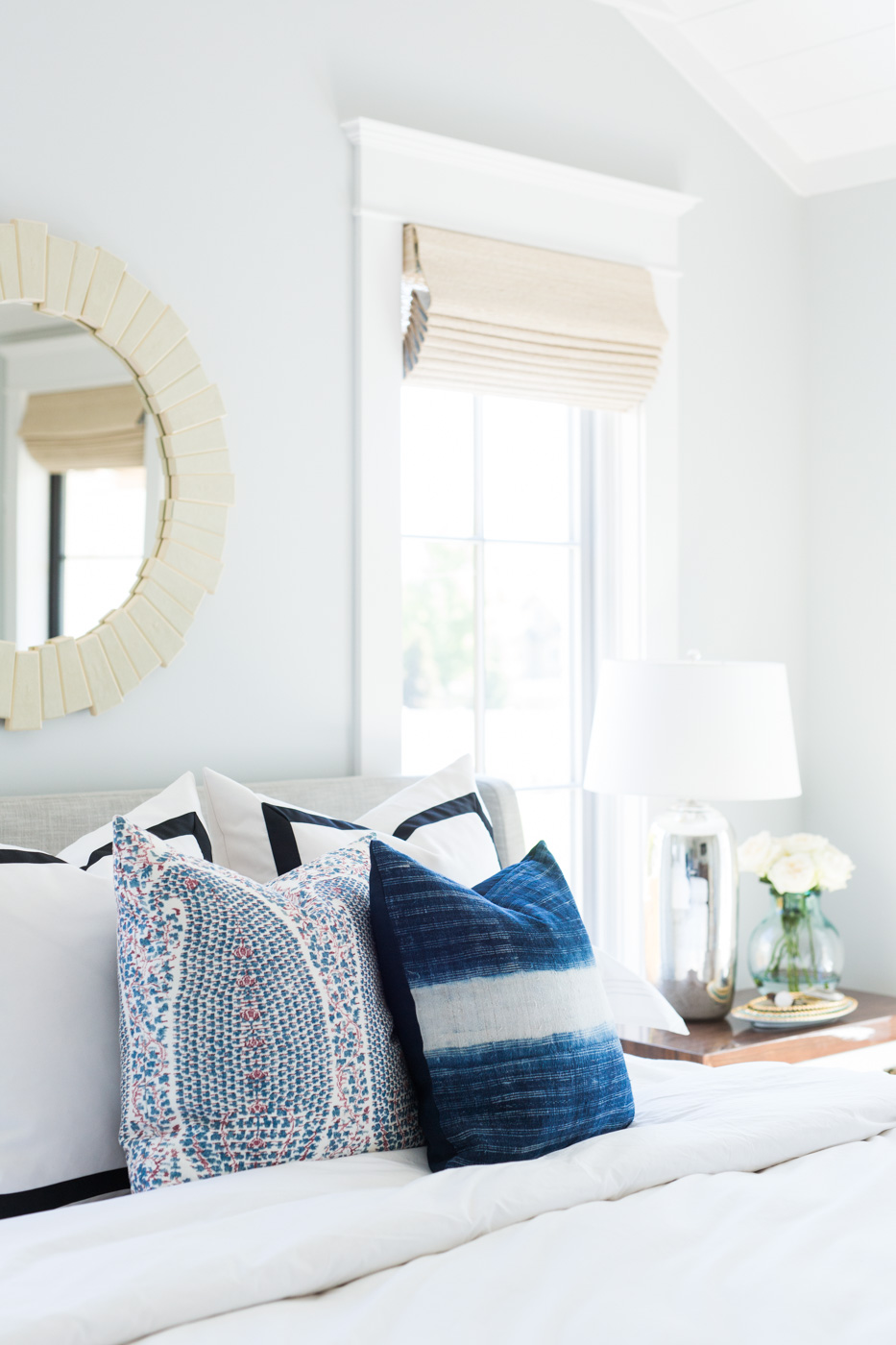 Decorative blue pillows on white bed
