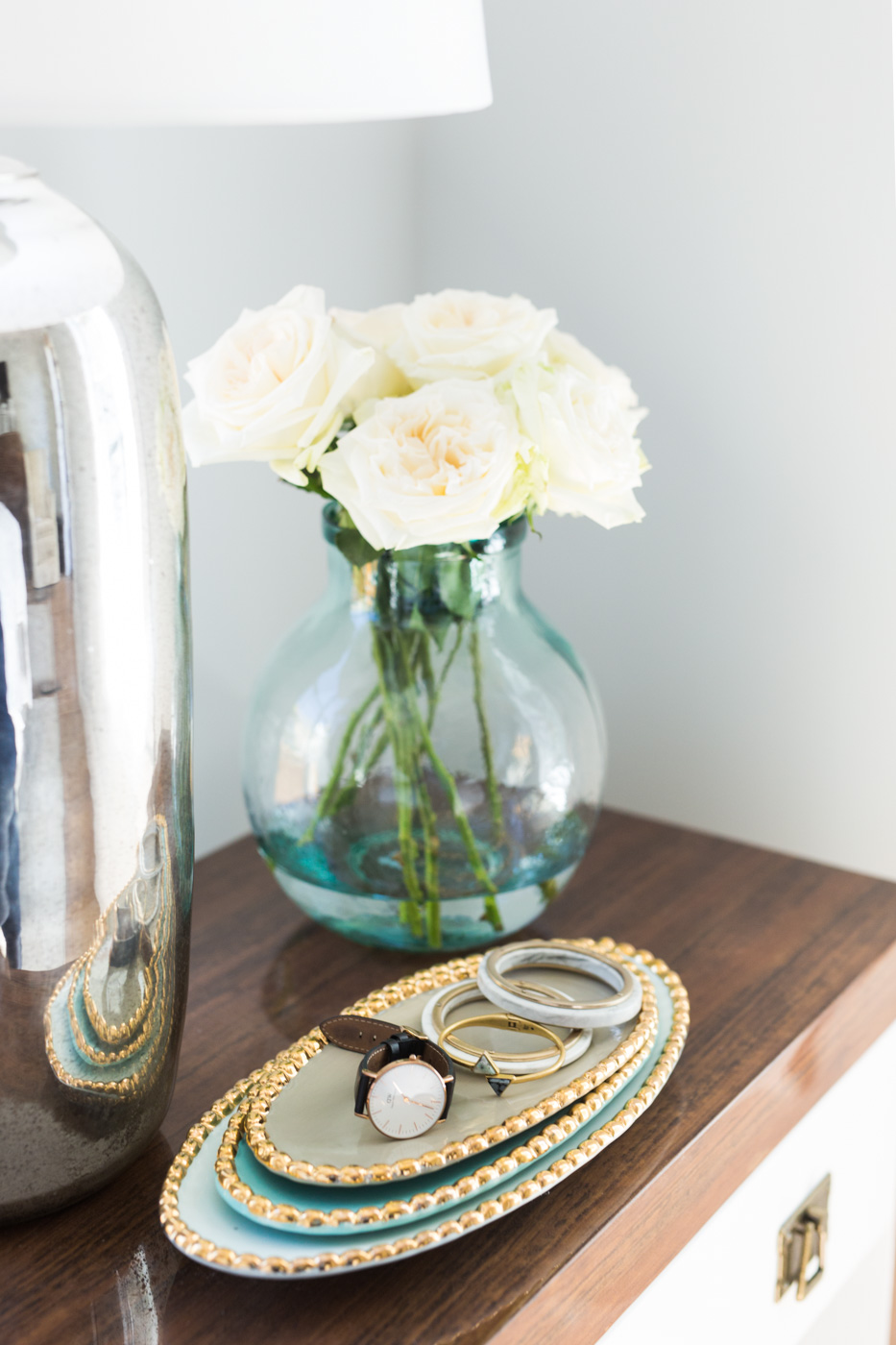 Decorative flowers and dishes on nightstand