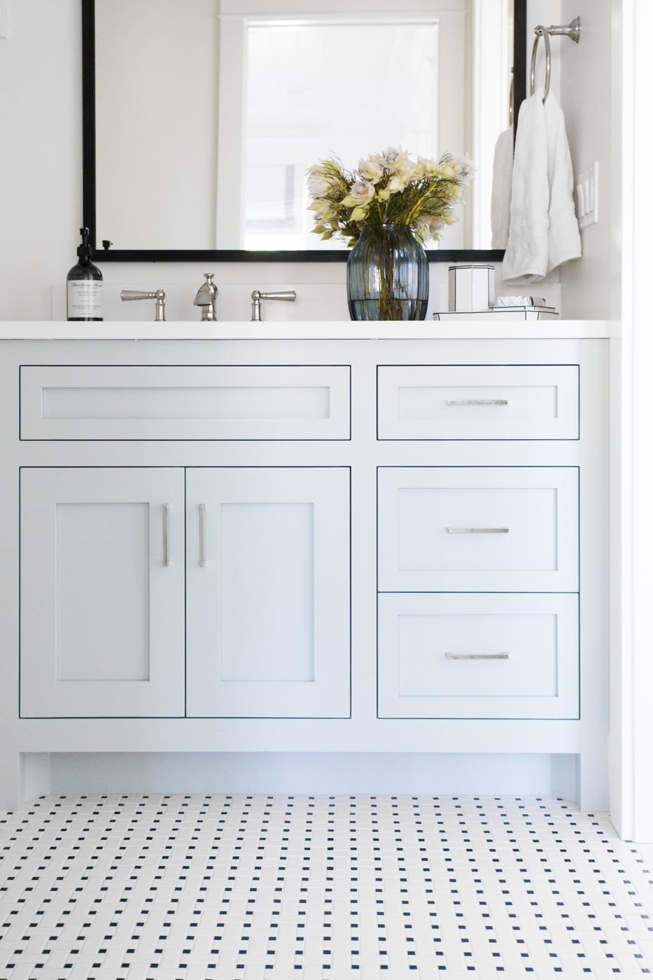 White vanity on small white tiles