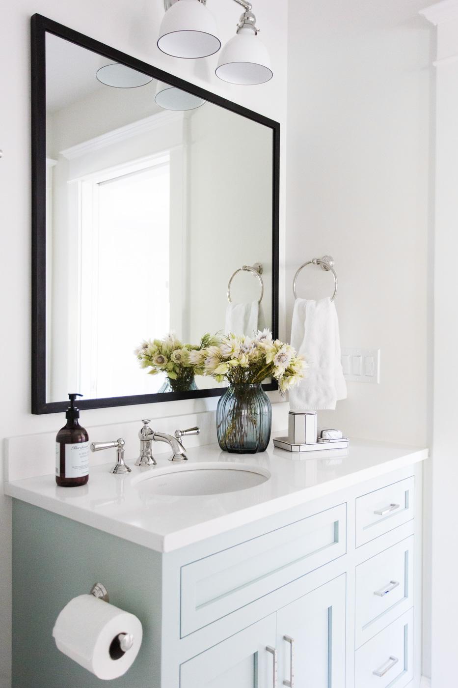 Large mirror behind white bathroom vanity