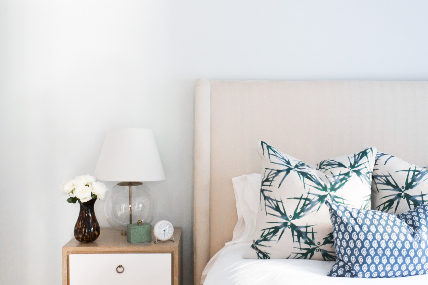 White and wooden nightstand next to white bed