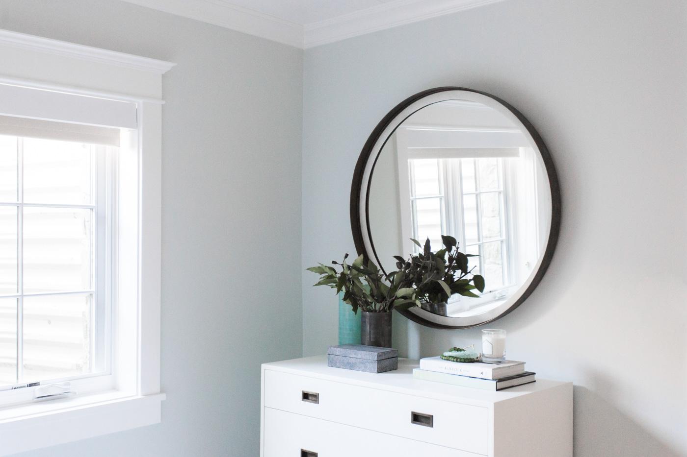 Circle mirror above white hutch
