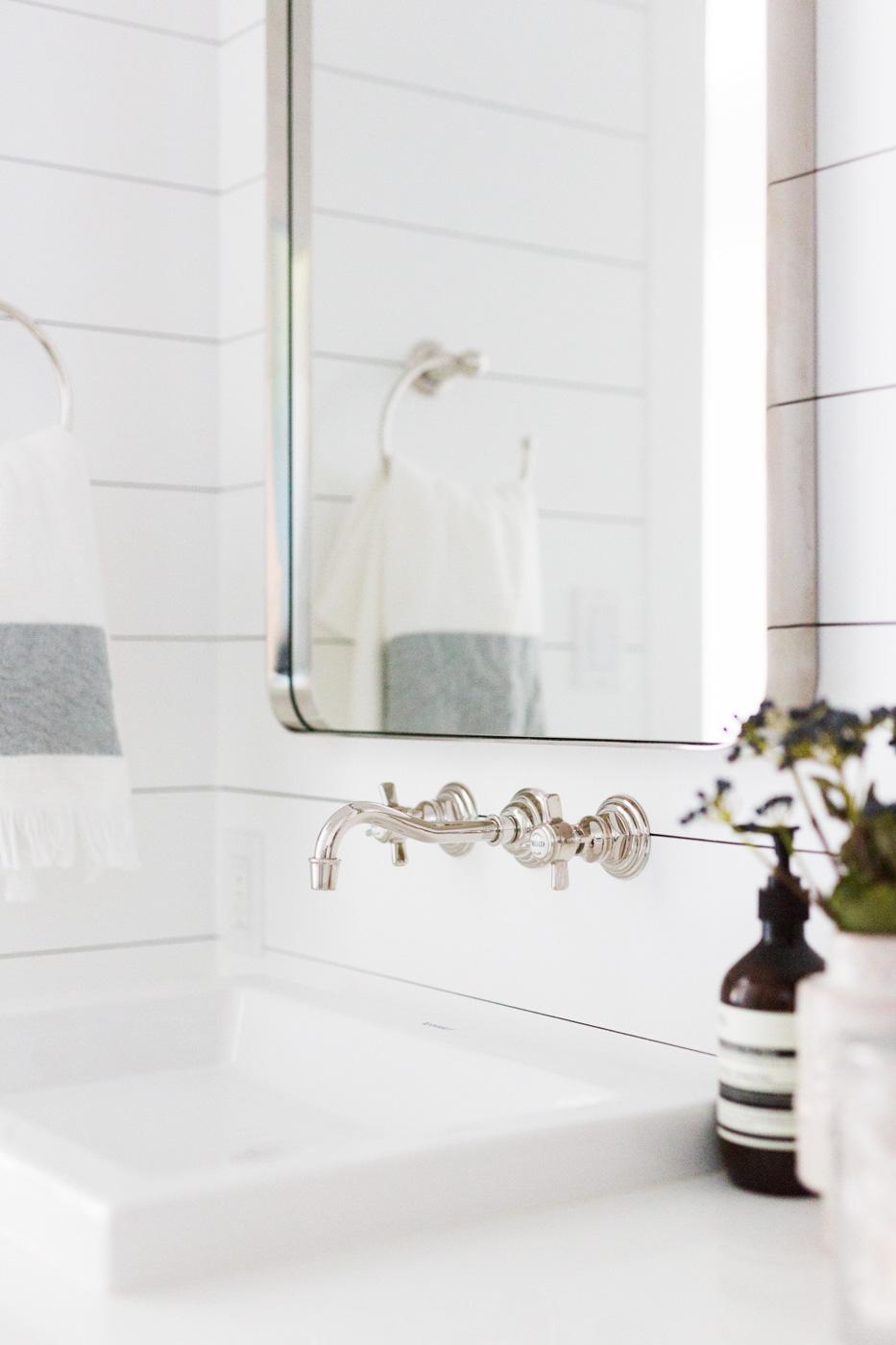 Mirror on wall against white tiled backsplash
