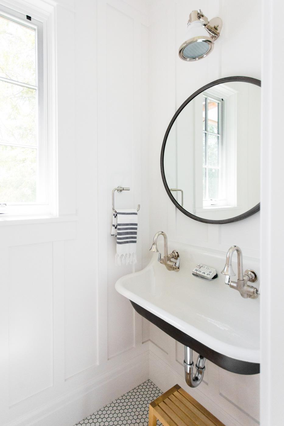 Large sink below circular mirror in bathroom