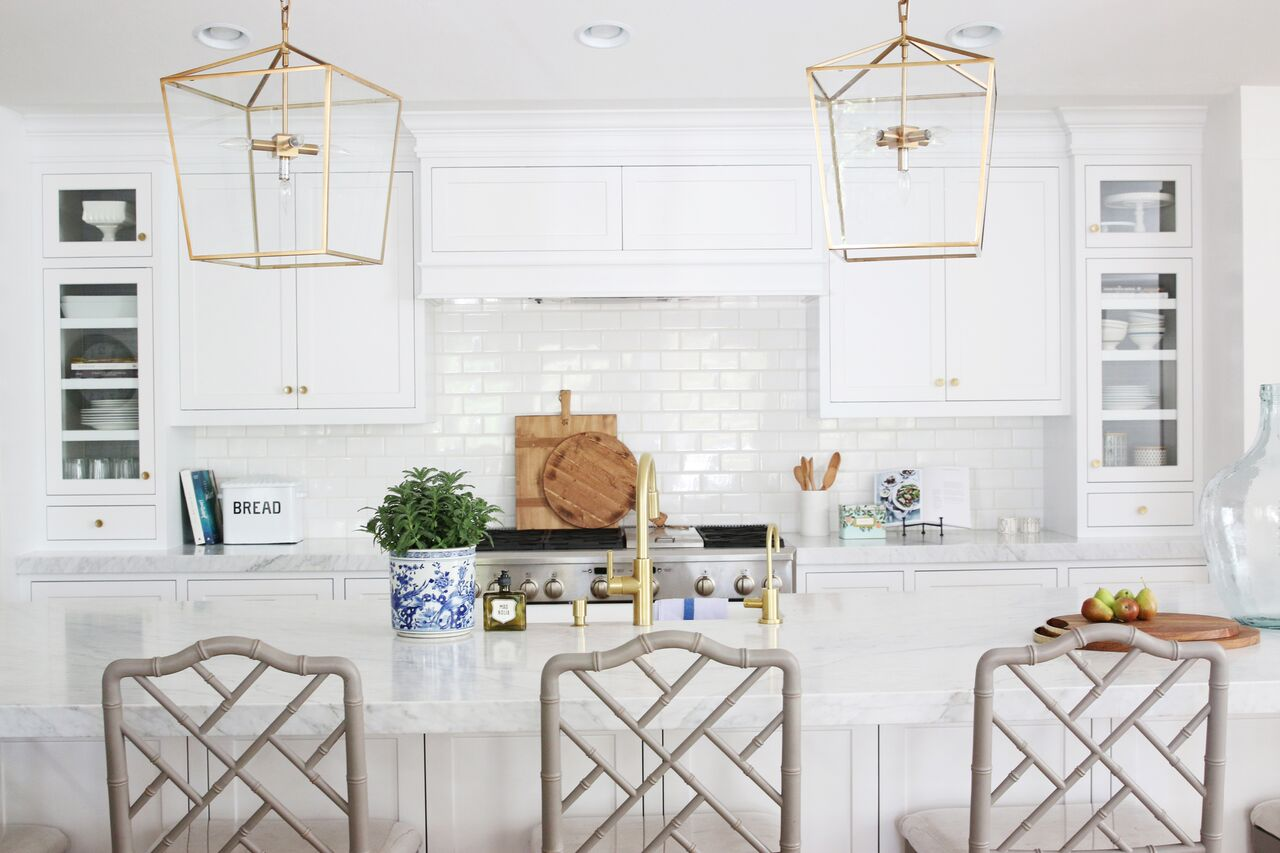 Gold lamp fixtures over kitchen island