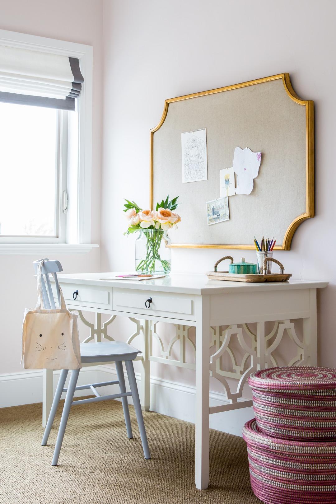 White desk with gold framed bulletin board