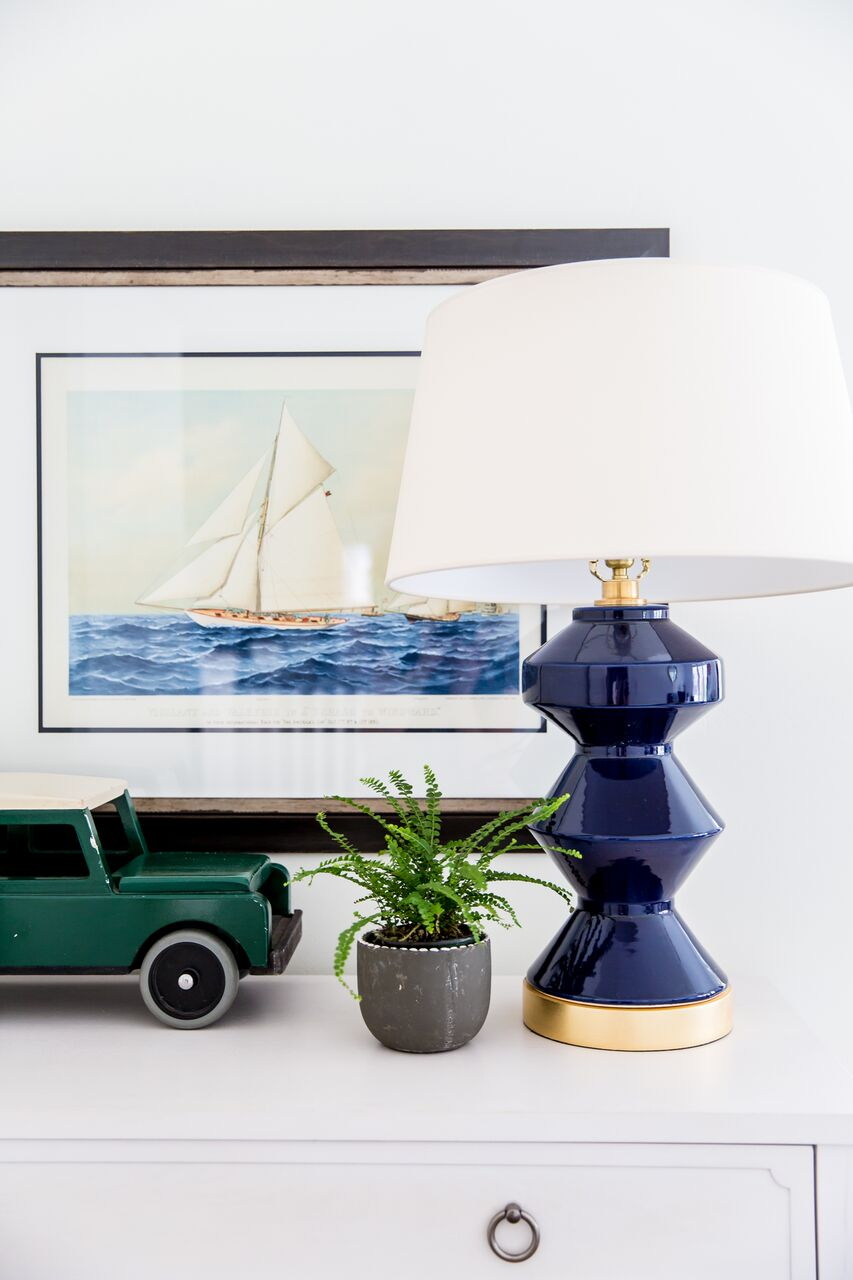 Lamp and car atop white dresser in bedroom