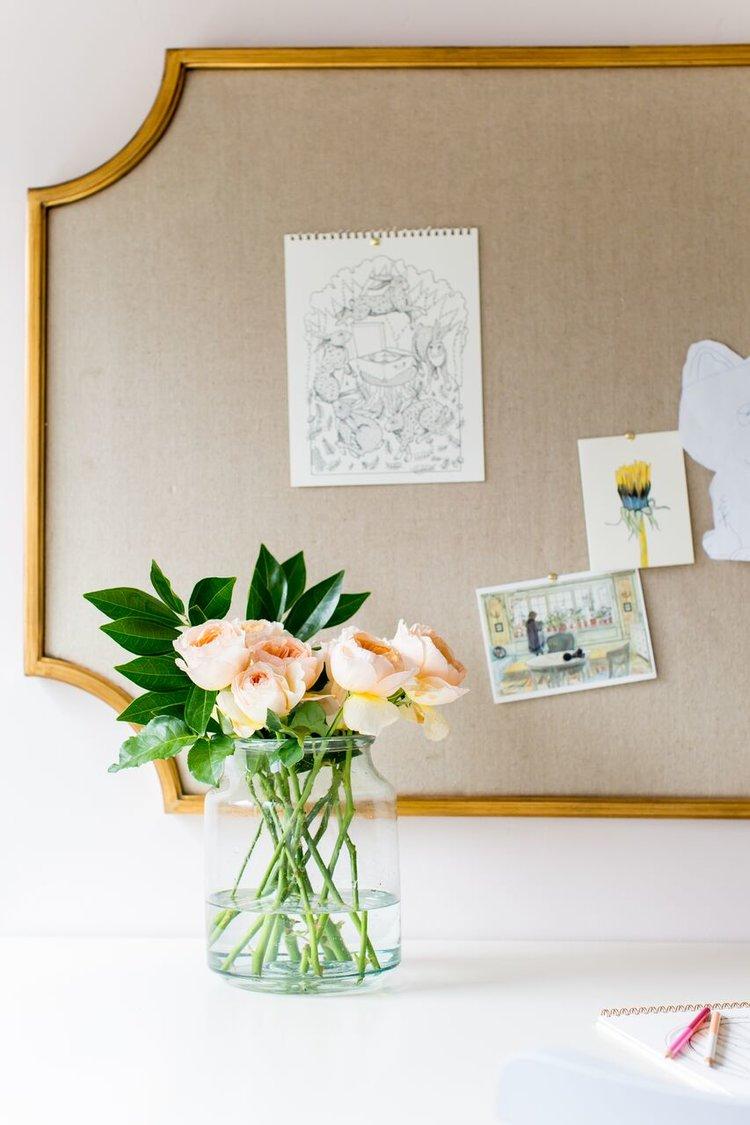 Flowers in vase in front of bulletin board