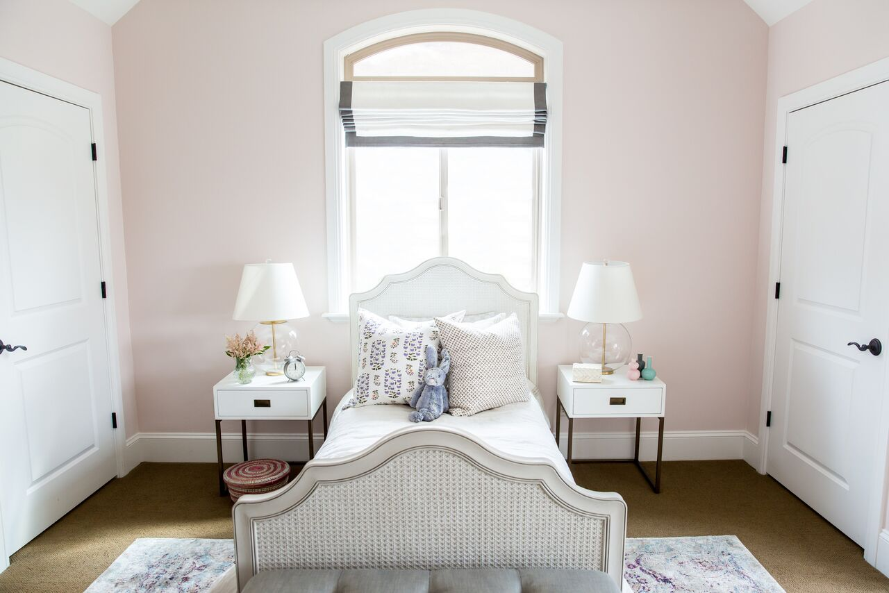 Twin bed with white headboard in front of window