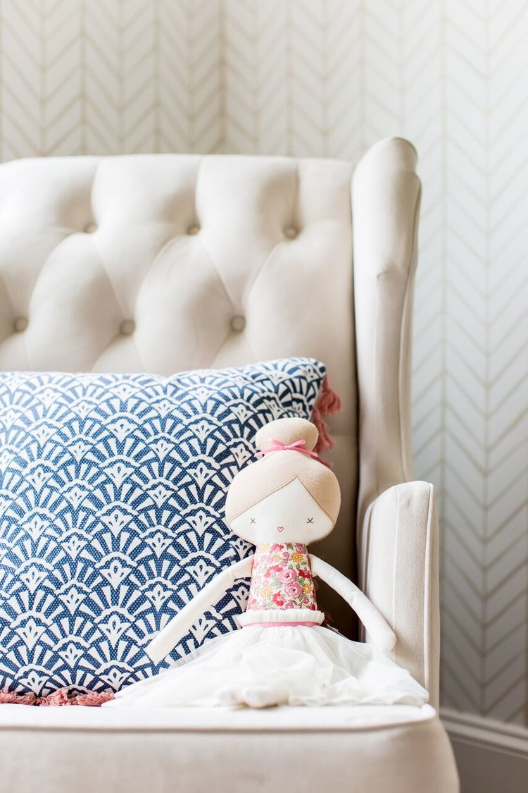 Doll sitting on sofa chair in bedroom