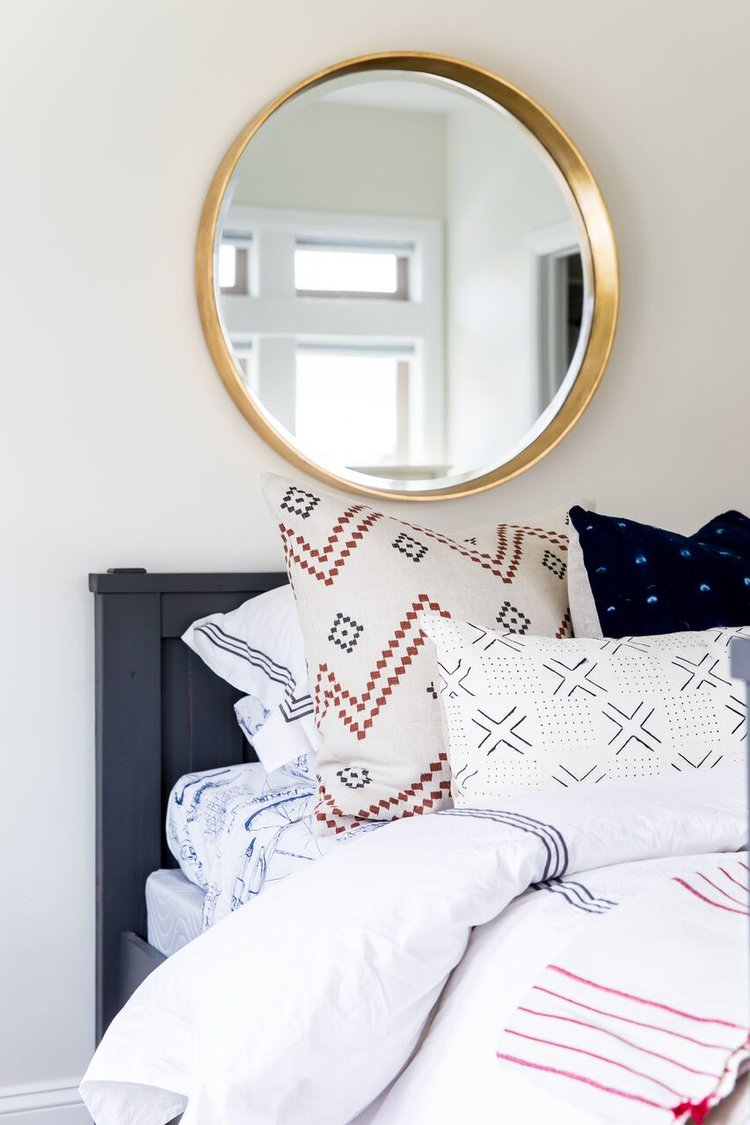 Gold rimmed mirror above twin bed