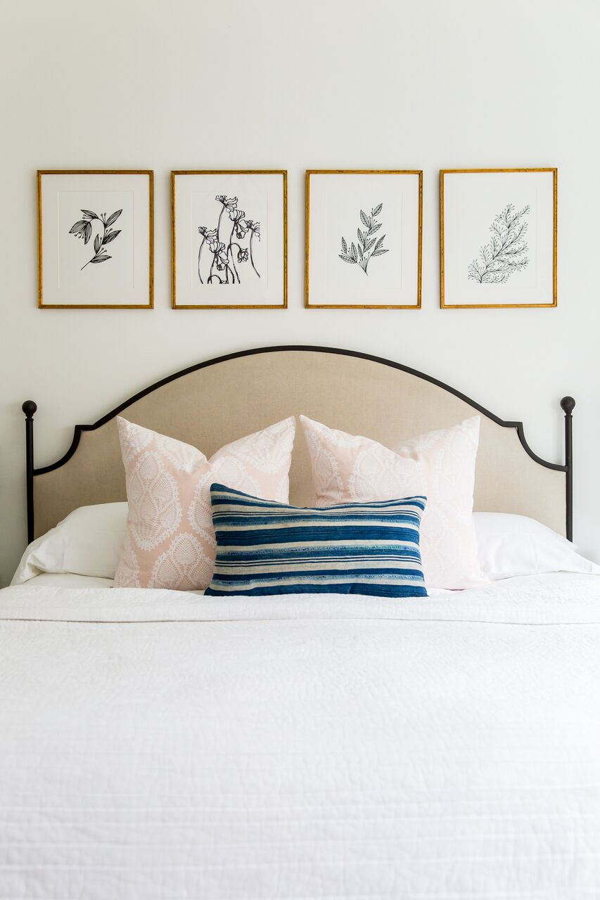 Four framed pictures along back wall above bed