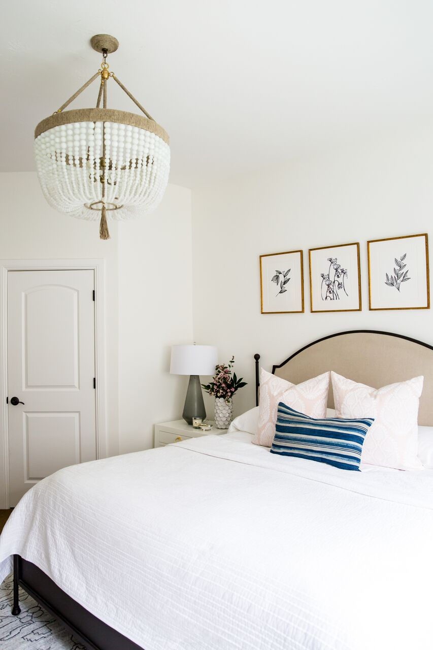 White bed with gold chandelier light fixture