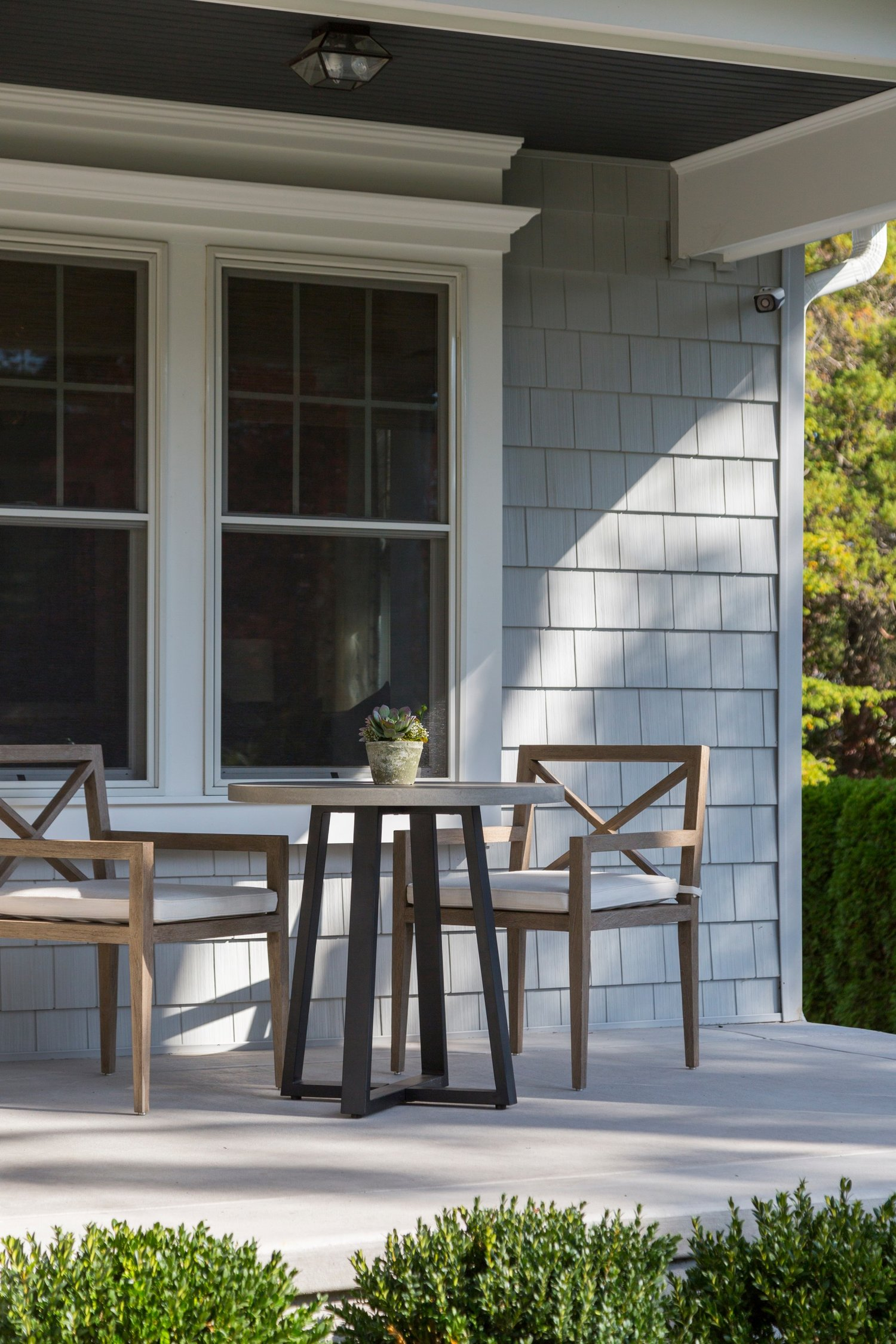 High table with two chairs in back porch