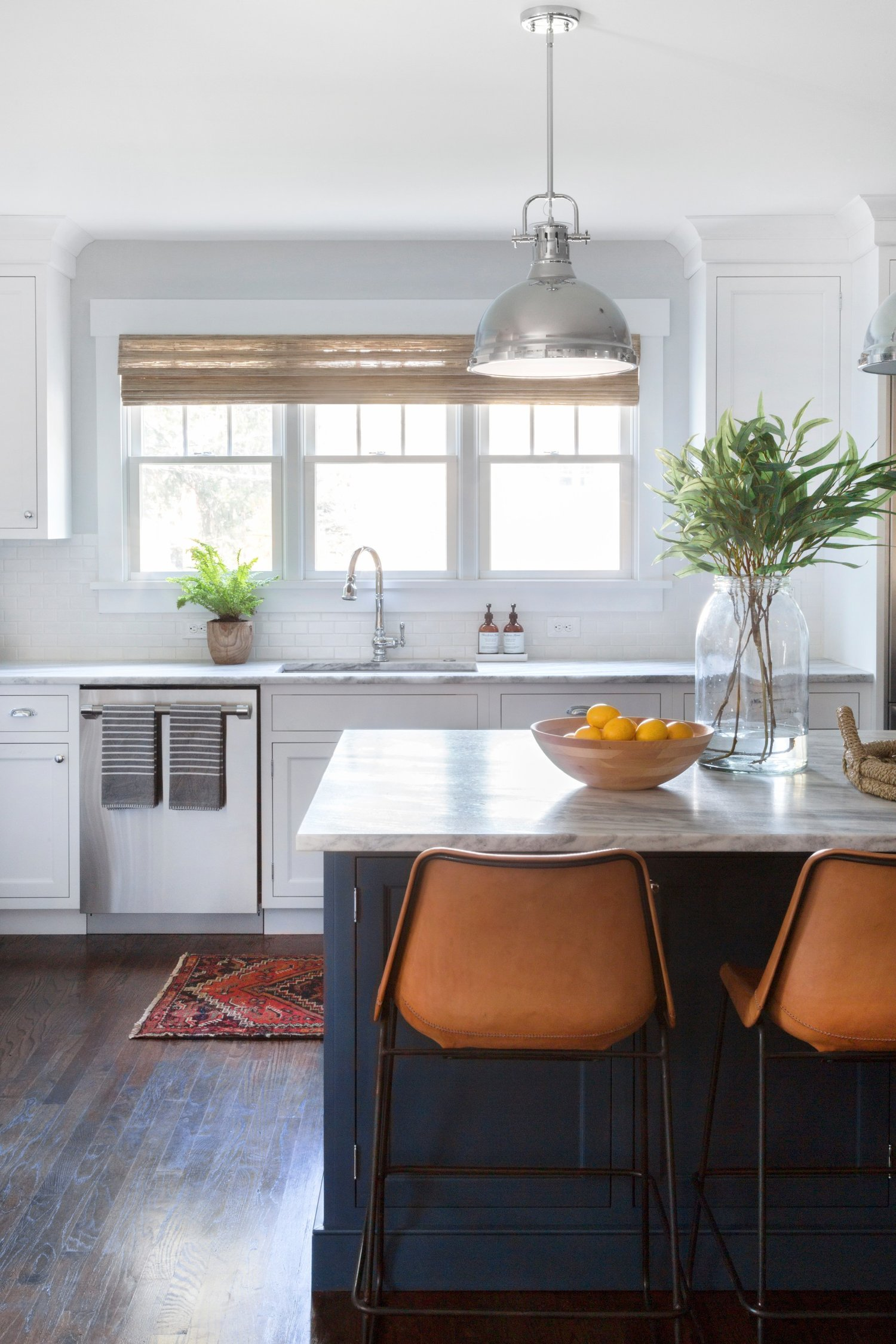 Orange chairs lined up along kitchen bar