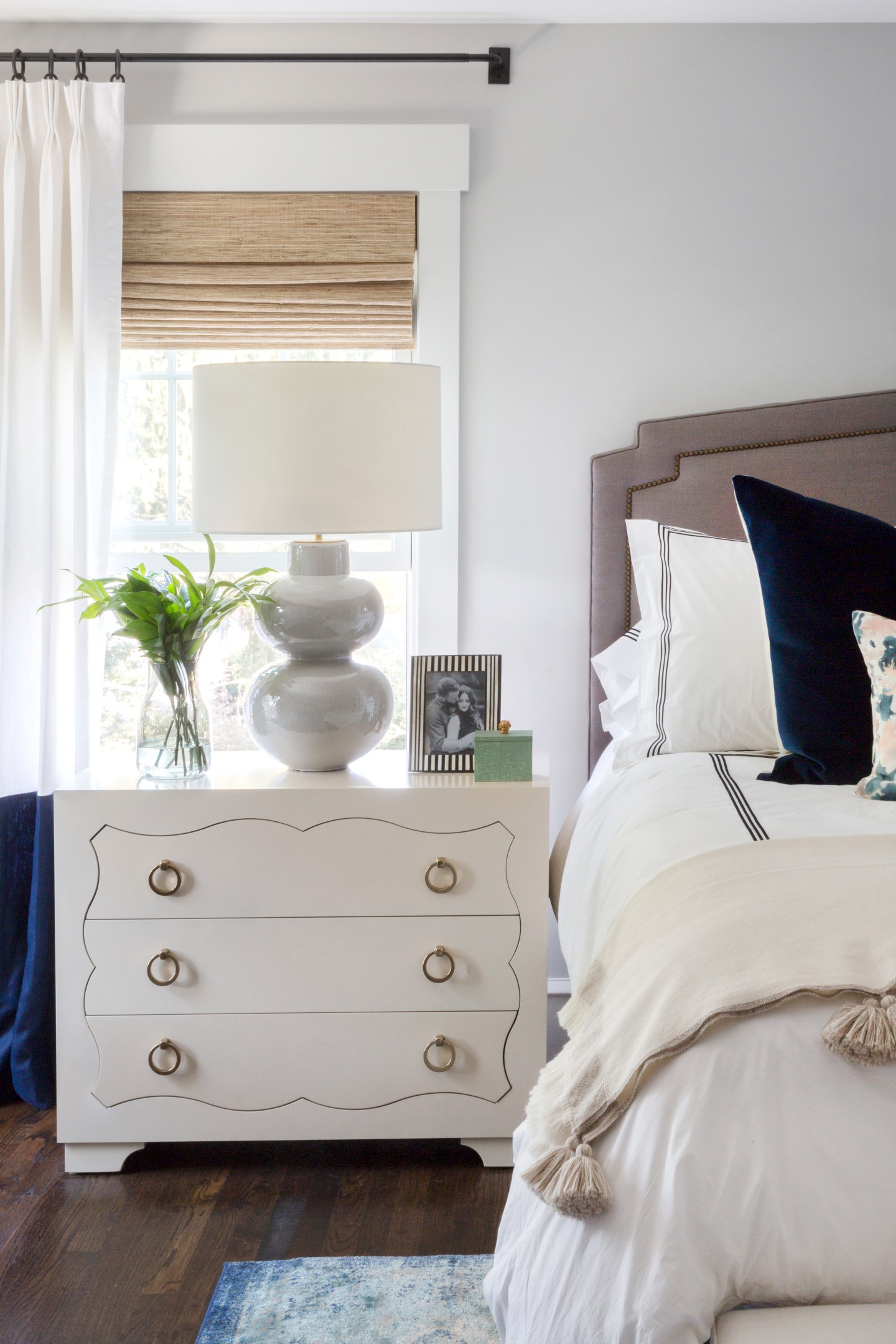 White nightstand next to master bed
