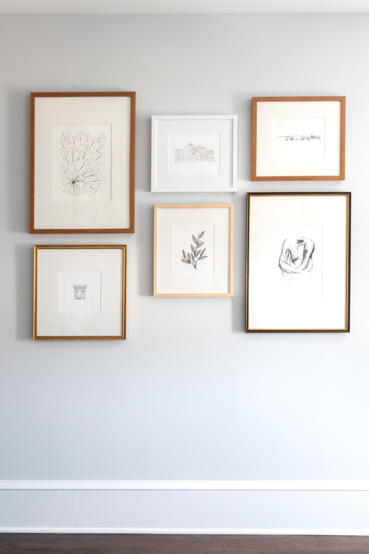 Arrangement of pictures along white wall