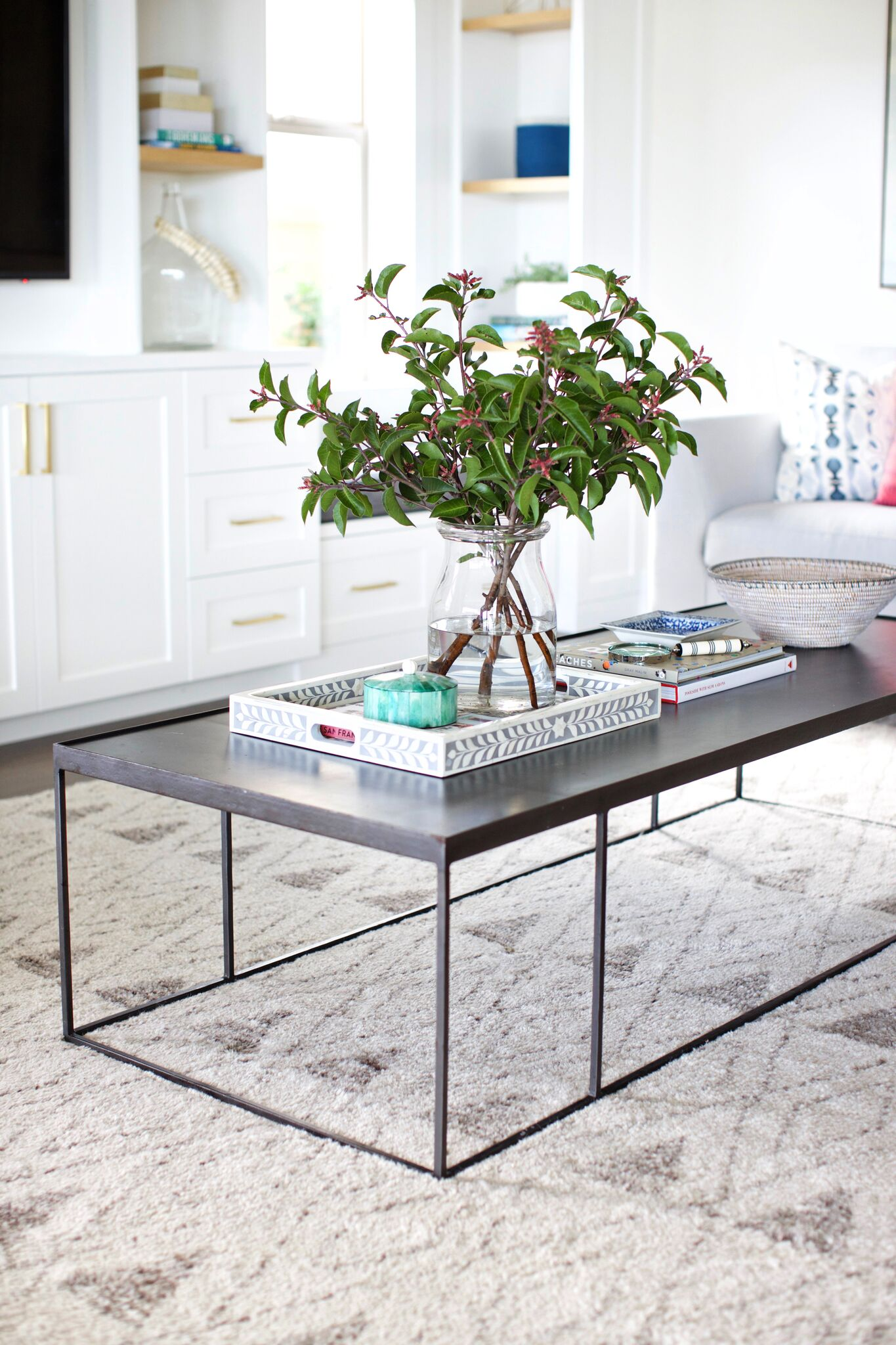 Large black coffee table with plants and items on top