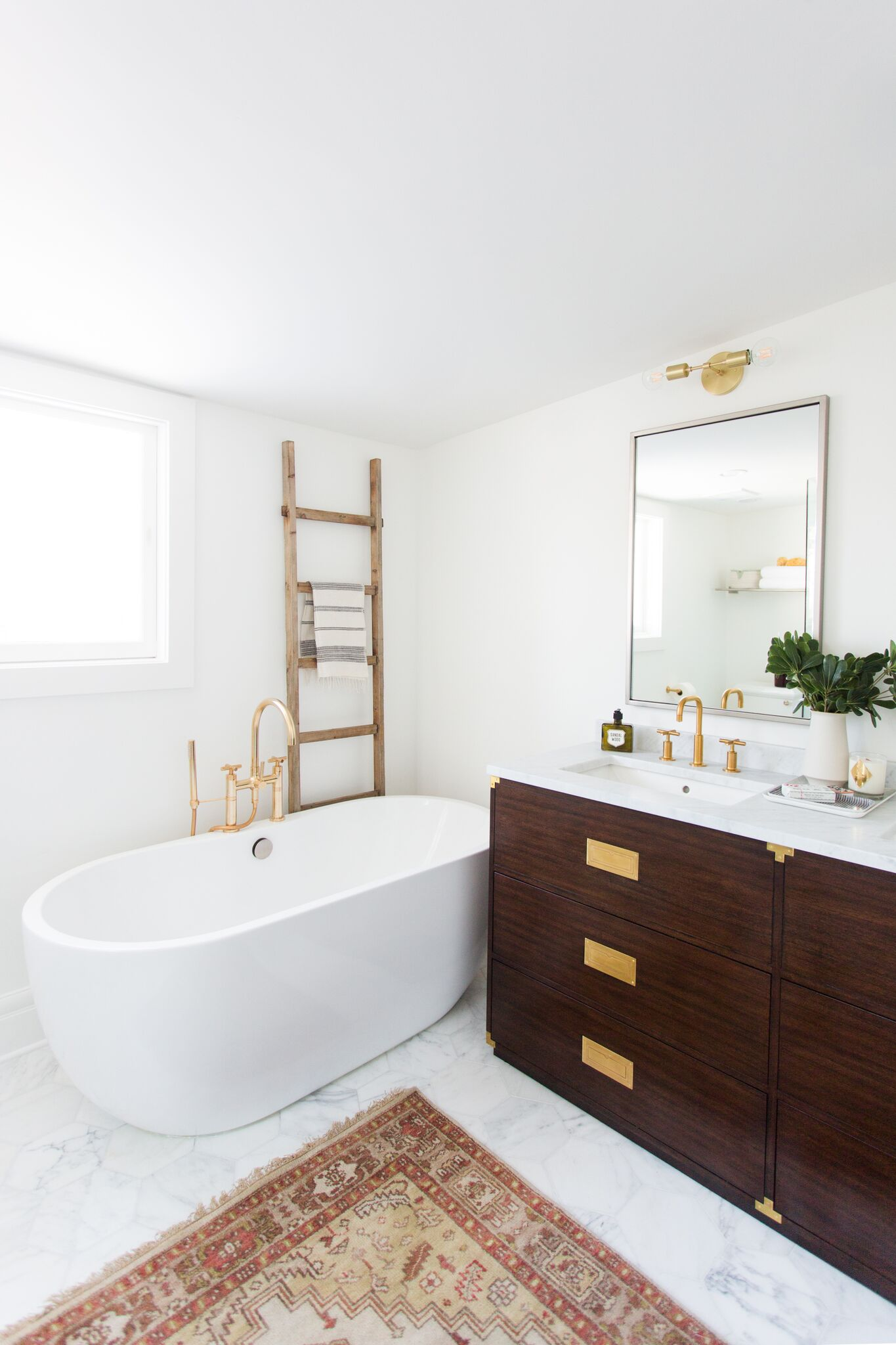 Large white tub with red area rug in bathroom