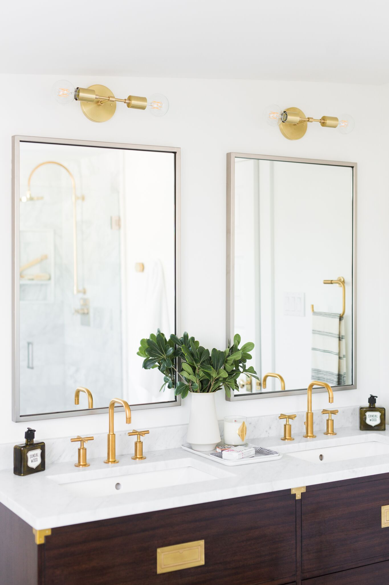 Gold light fixtures above the double mirrors