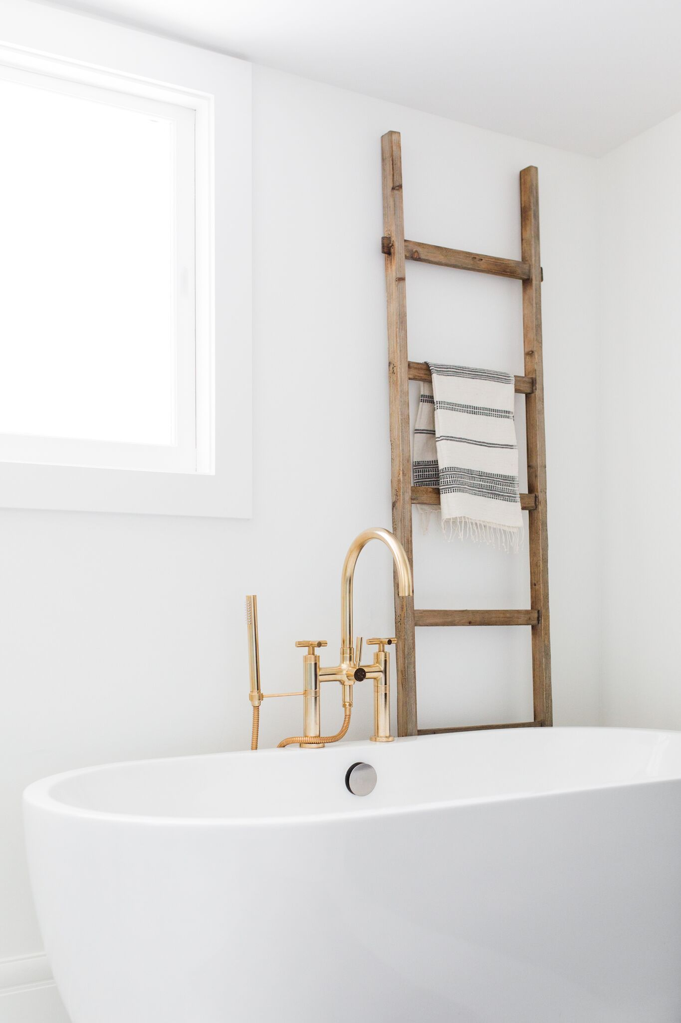 Small wooden ladder standing behind tub
