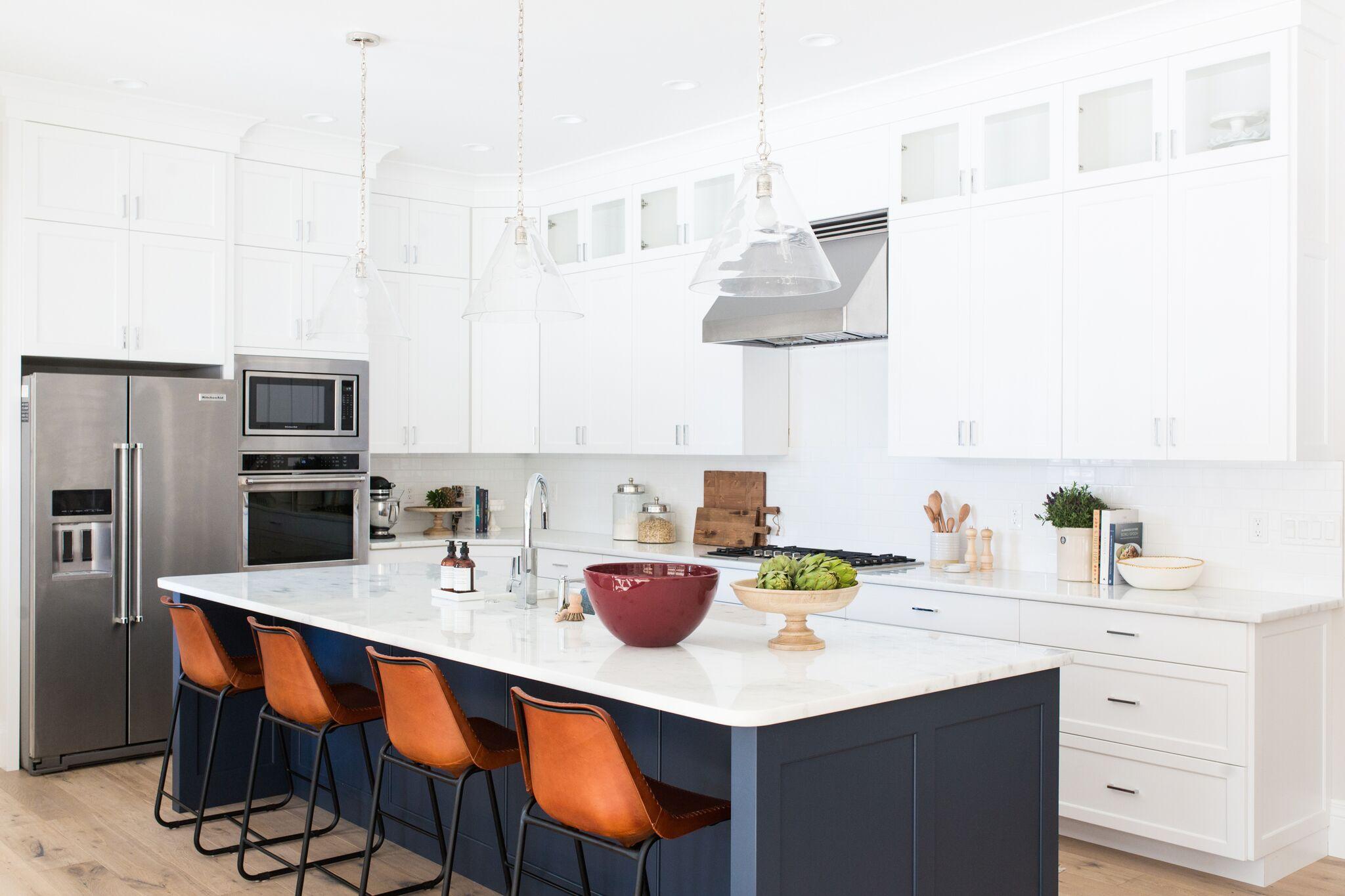 Four orange chairs underneath kitchen island