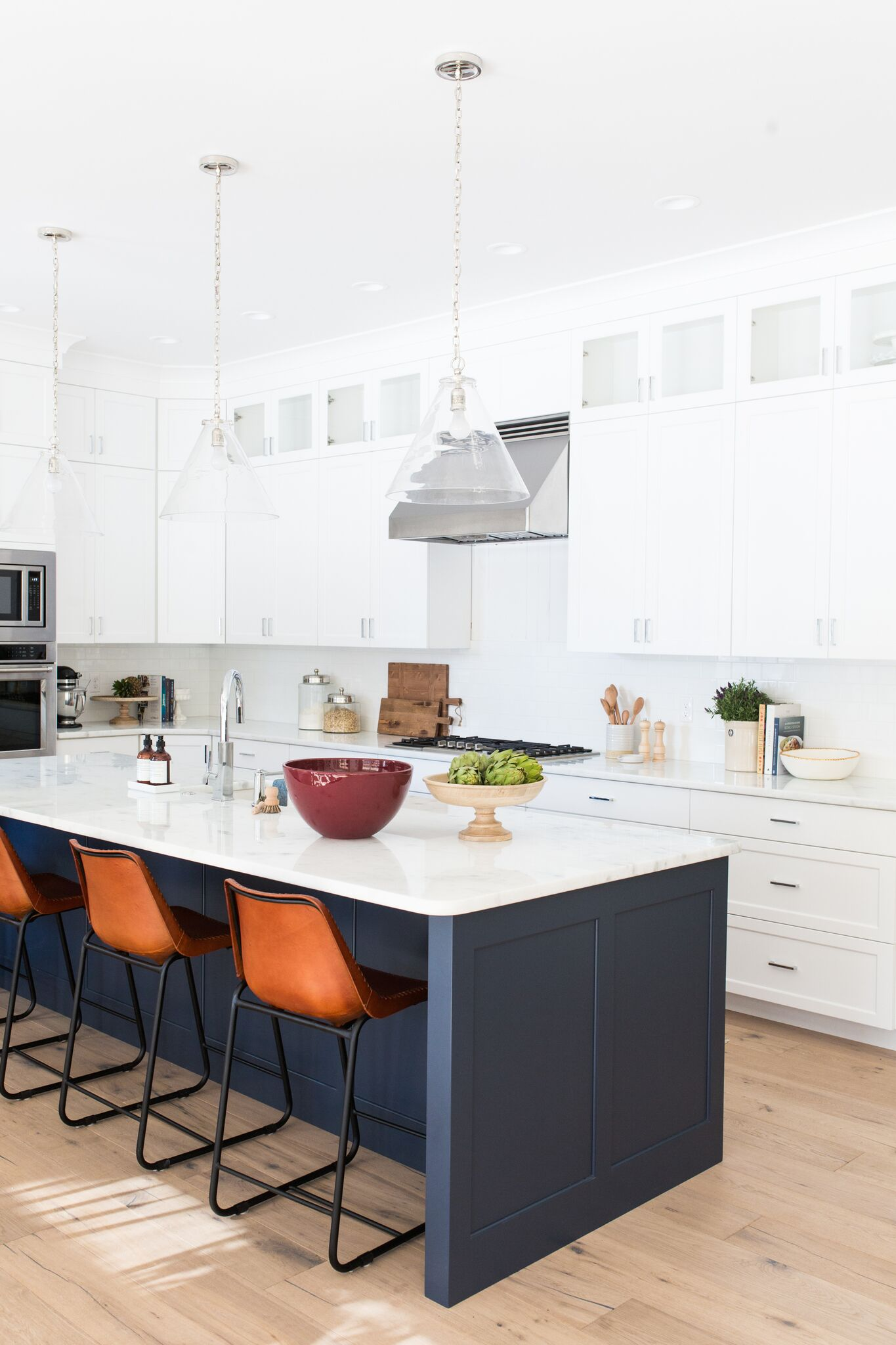 Orange stools with the white counter top island