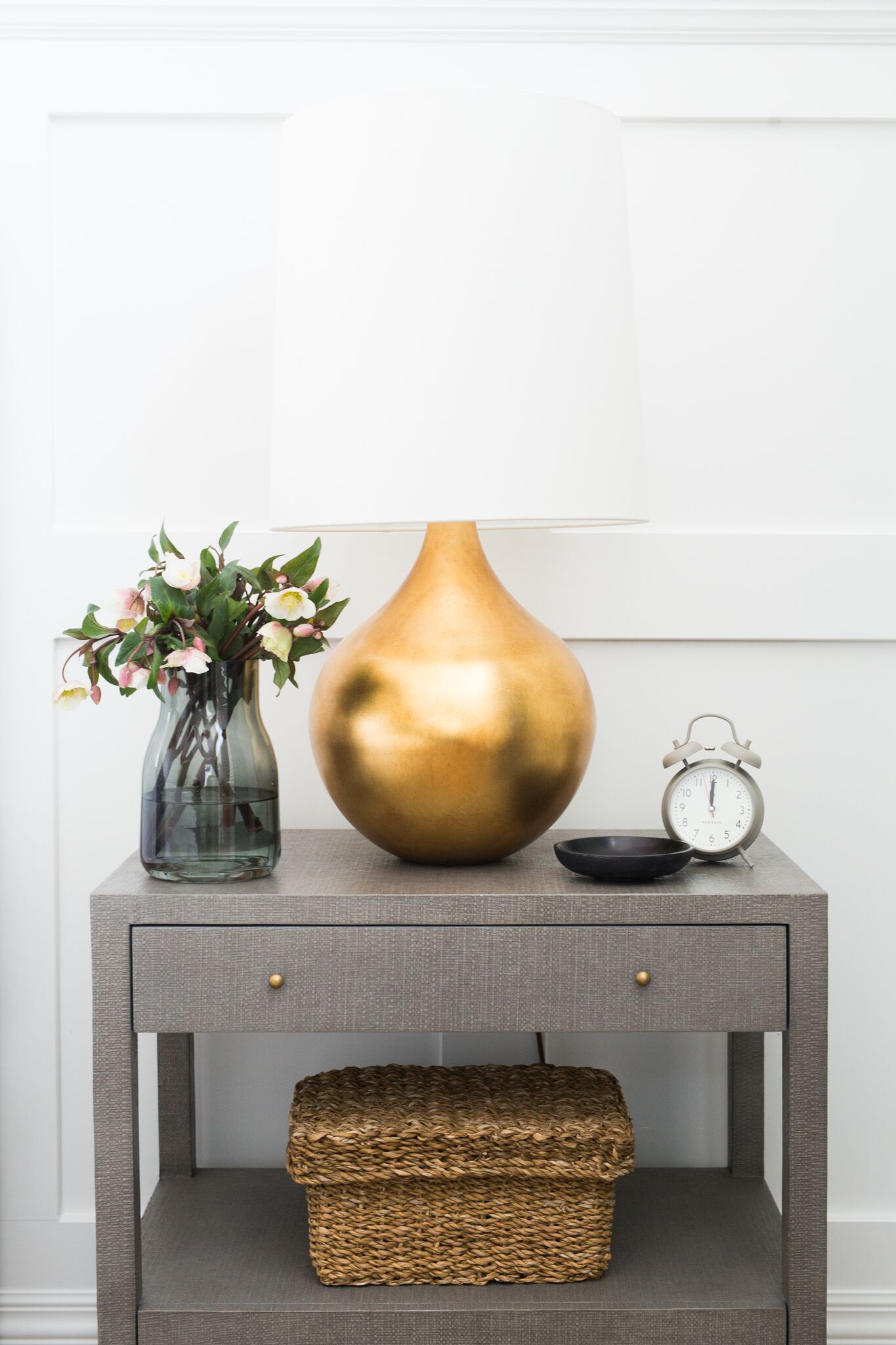 Large golden lamp on top of wooden hutch