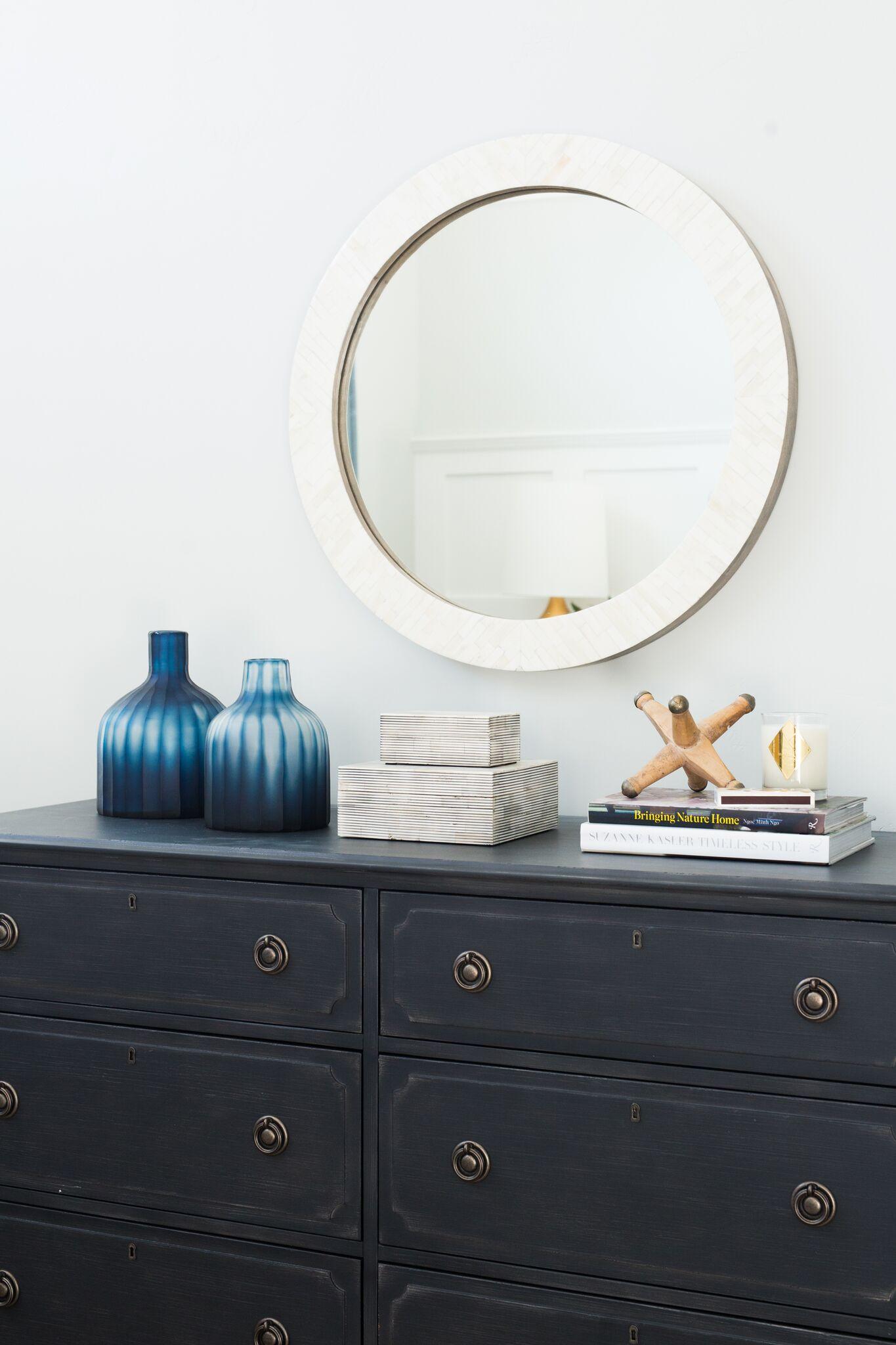 Round white mirror on black vanity