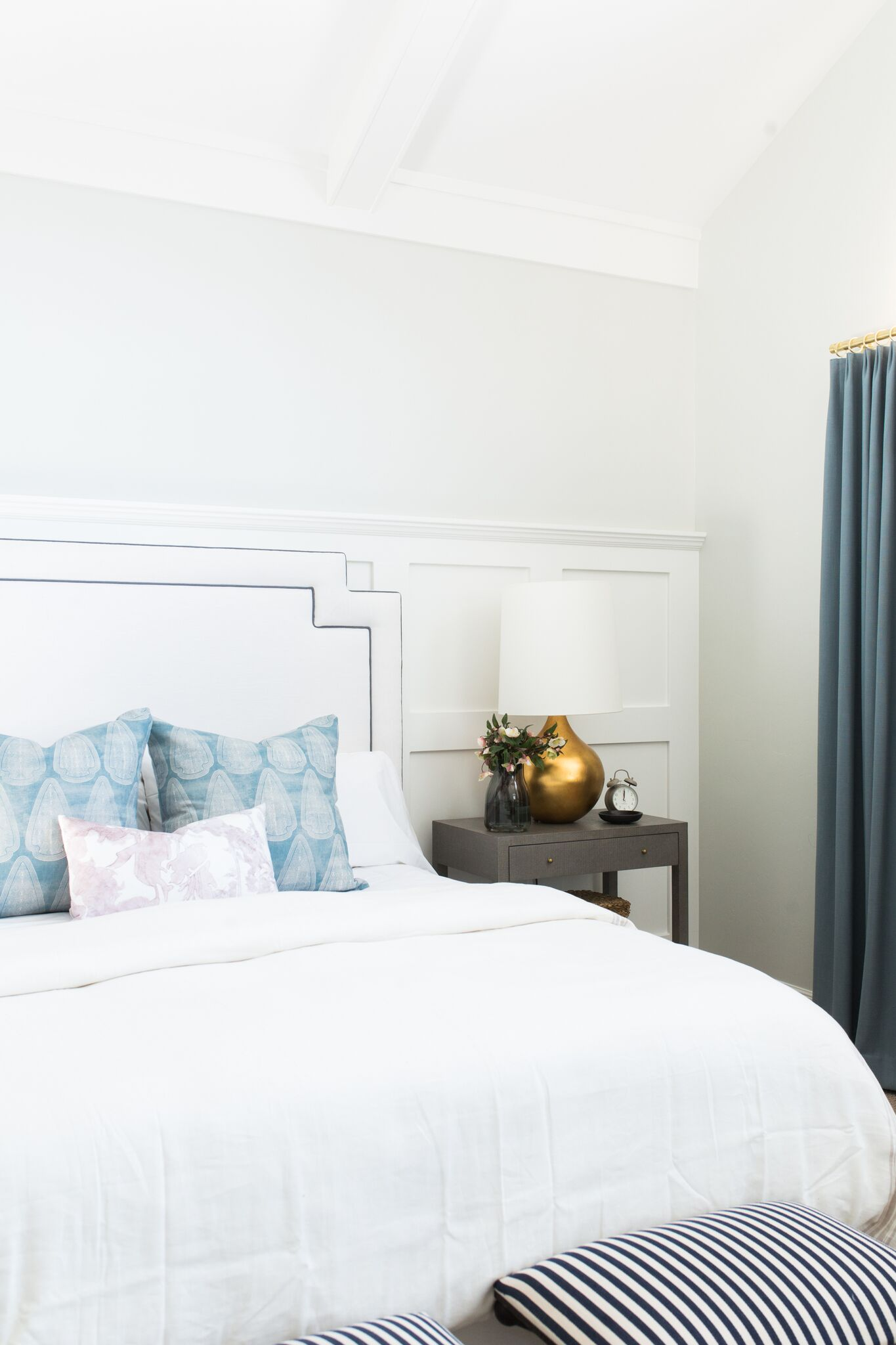 White bed next to grey nightstand