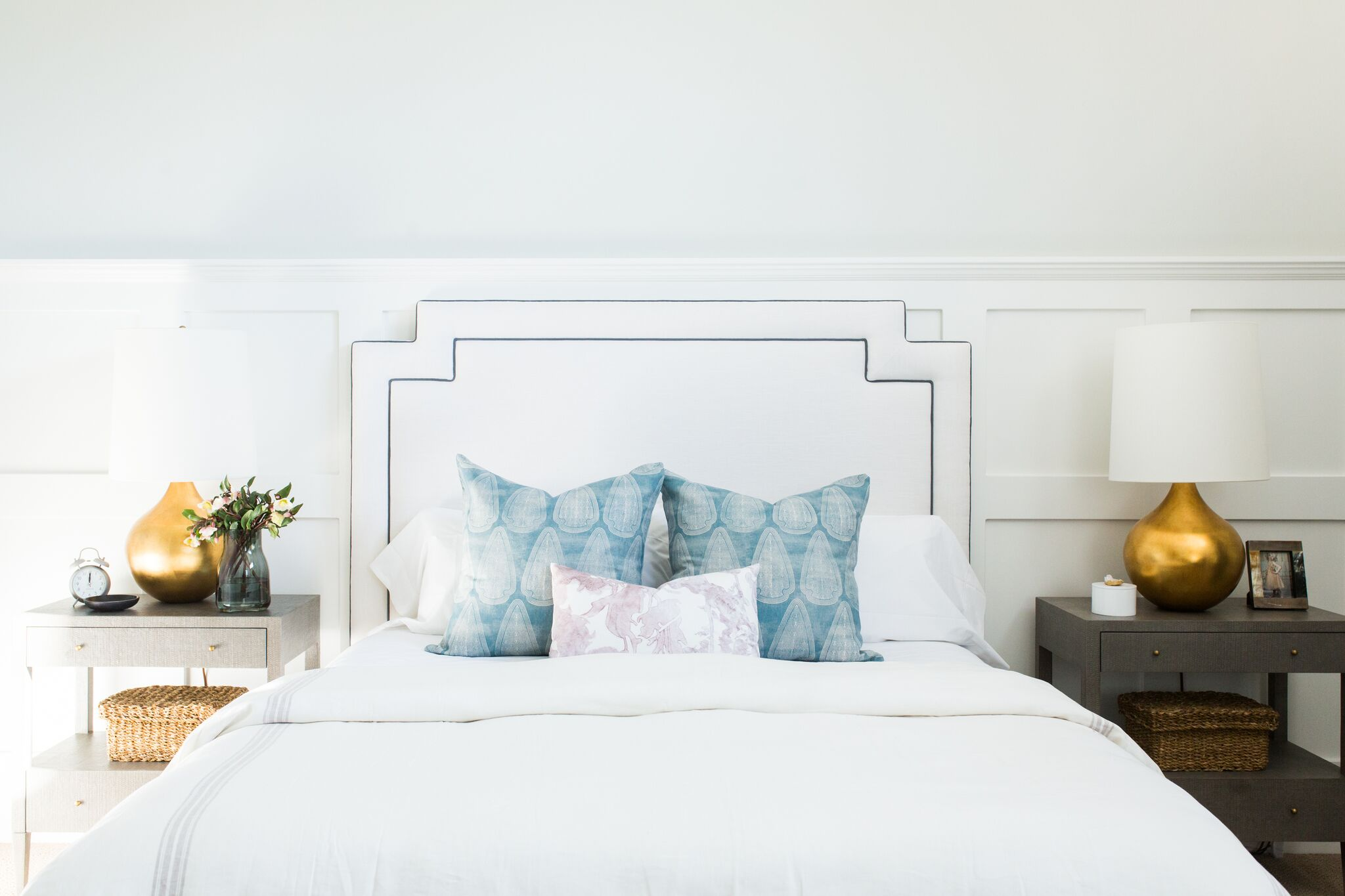 White master bed with blue decorative pillows