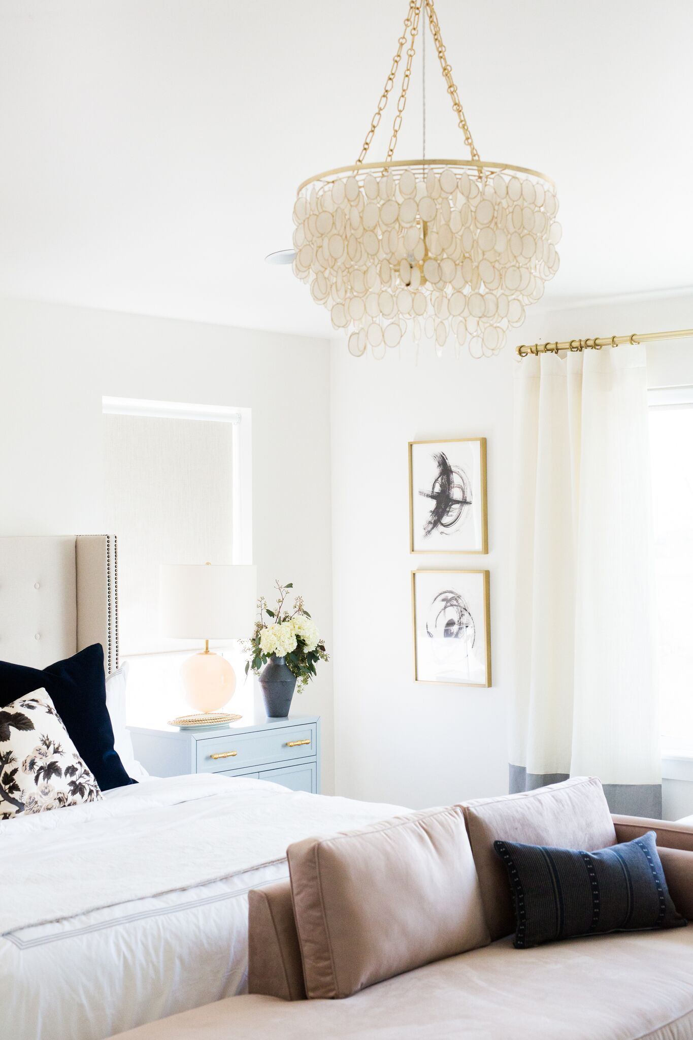 Side of bed with large light fixture and pictures in bedroom