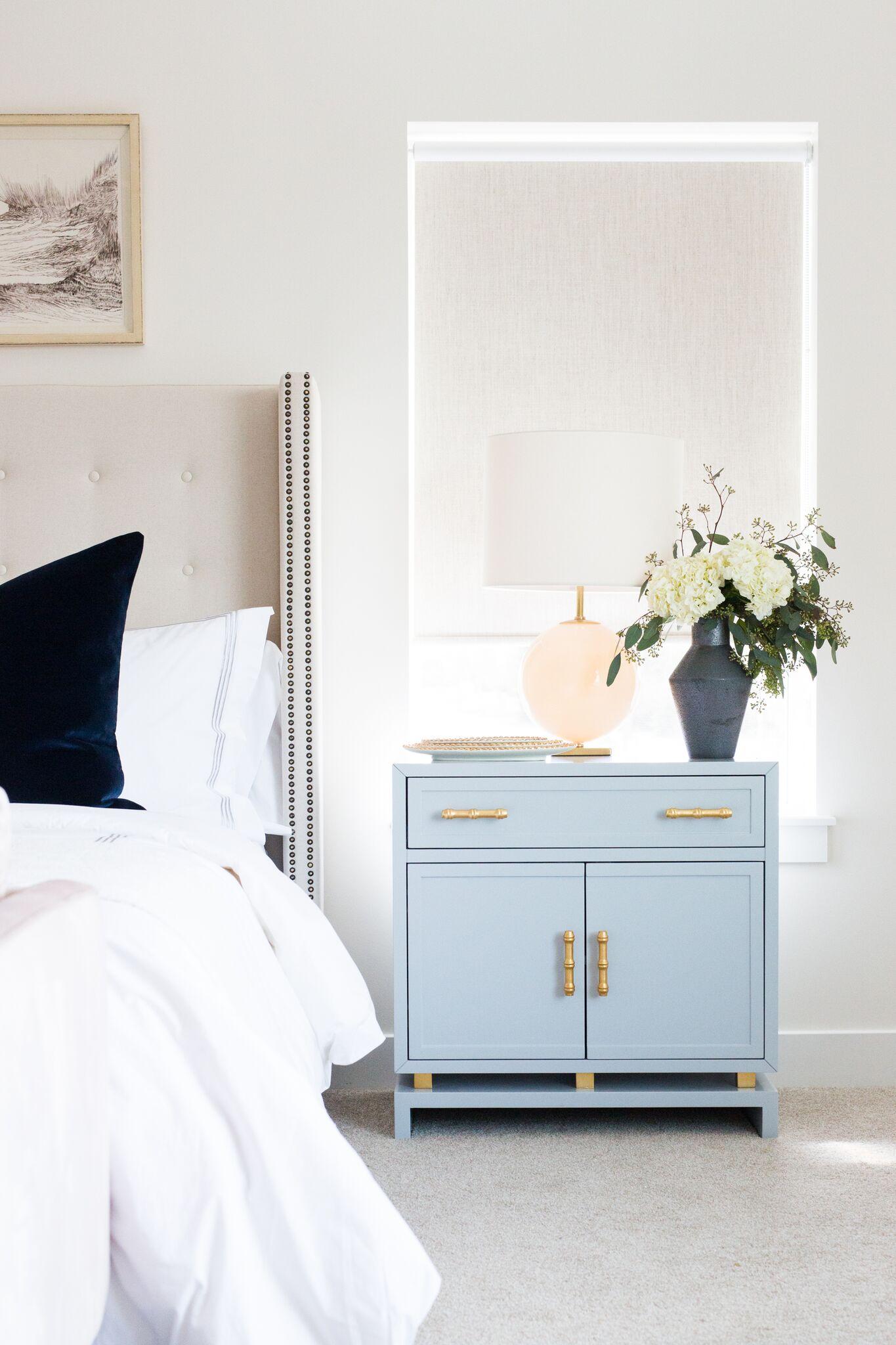 Powder blue nightstand next to white bed