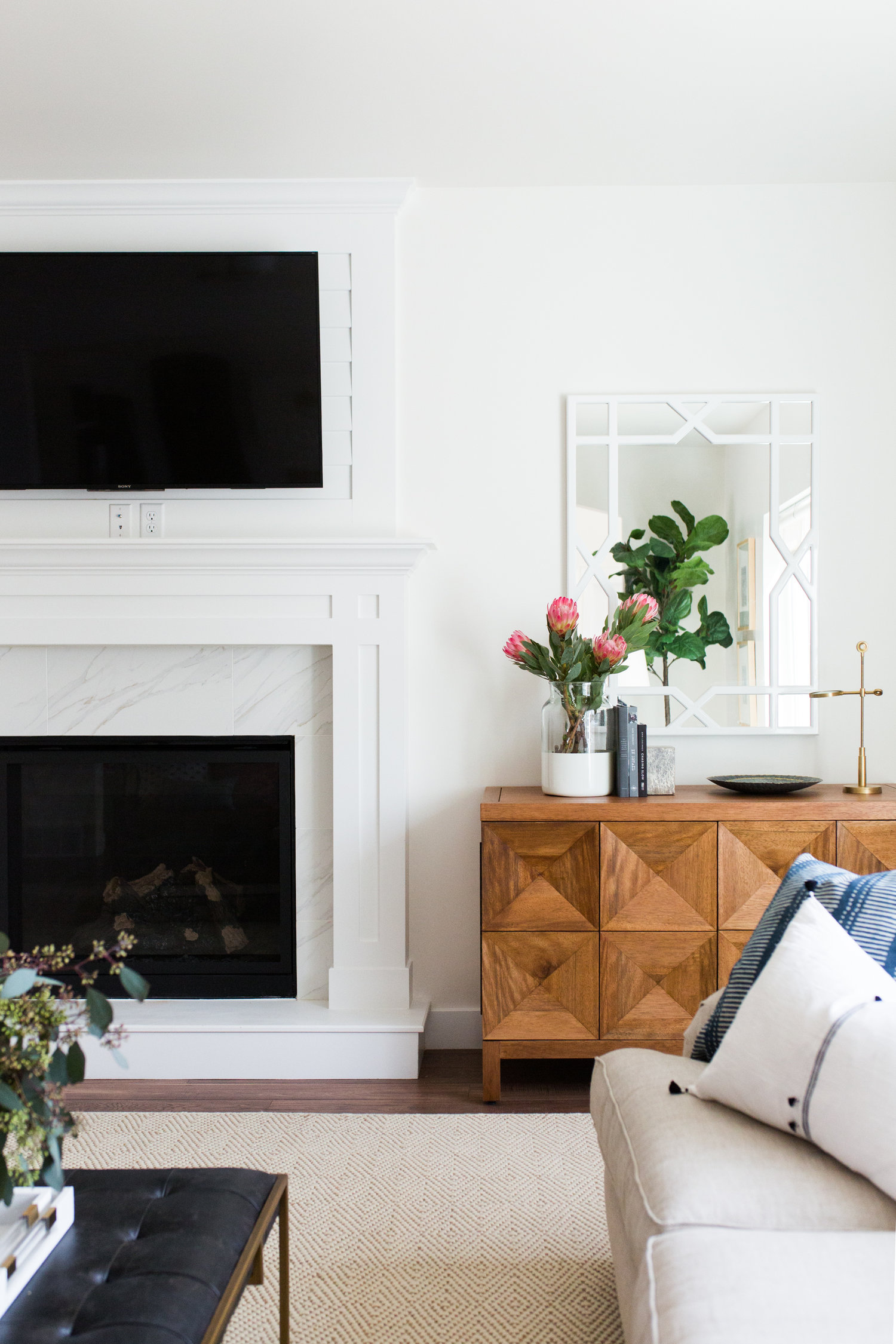 White love seat in front of white fireplace