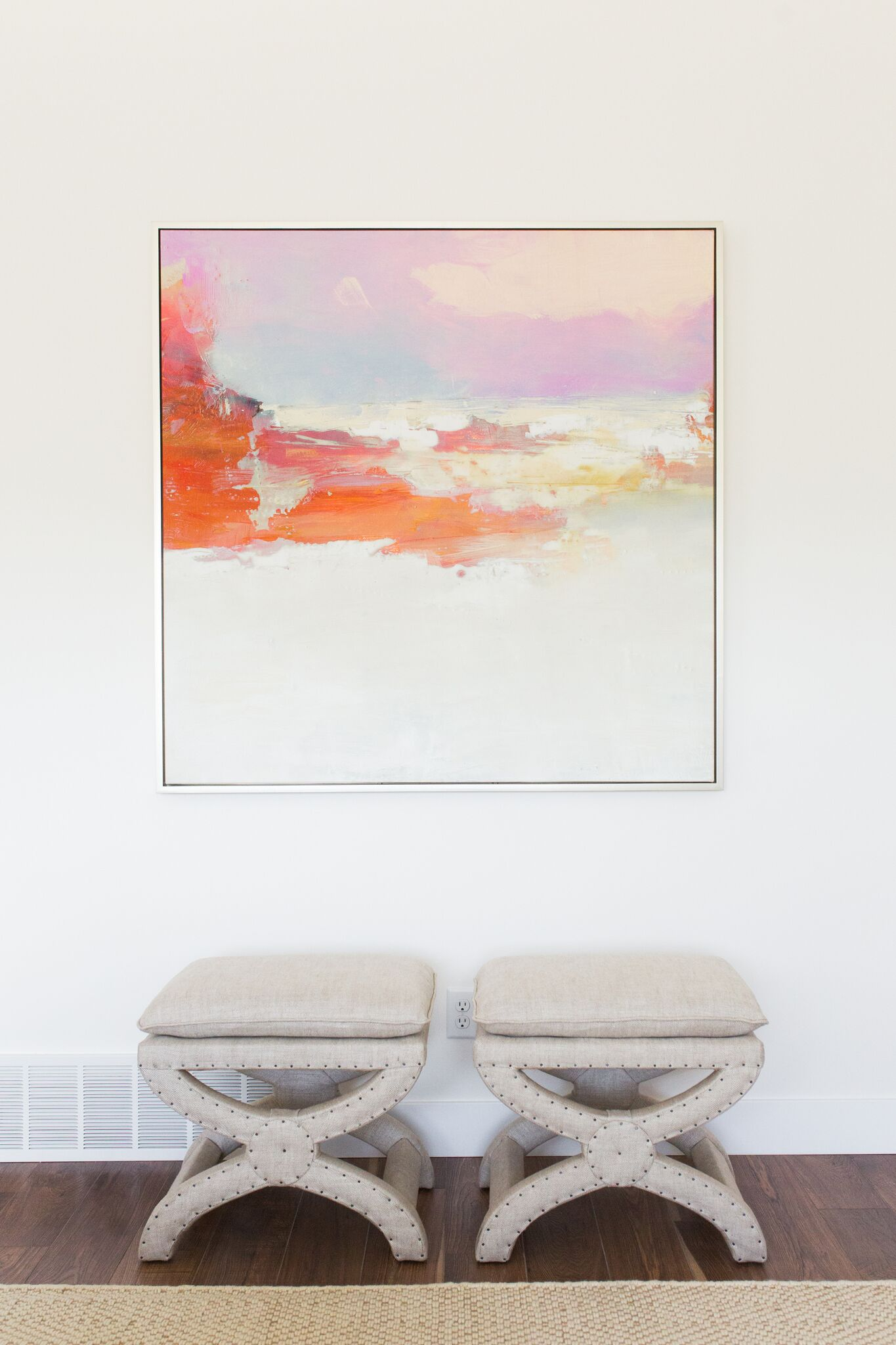 Two small, white stools with white cushions