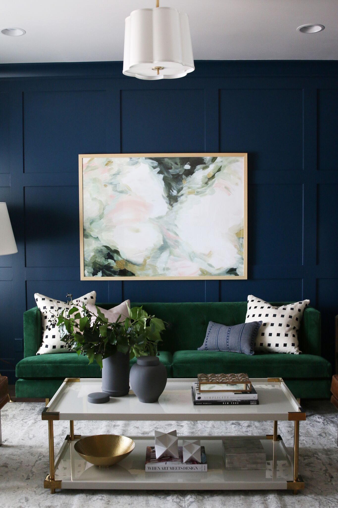 Green couch underneath white artwork