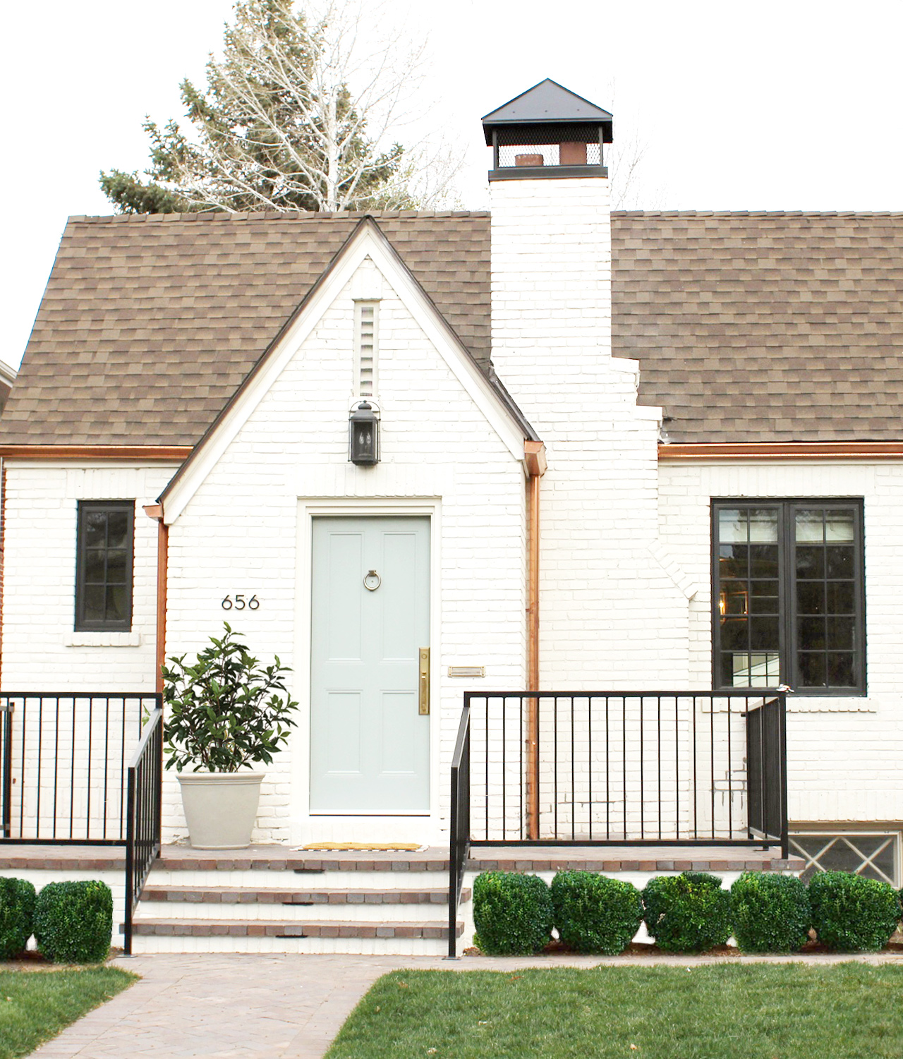 """White Brick Tudor House and Front Door in Benjamin Moore's """"China White"""" and """"Greyhound"""""""